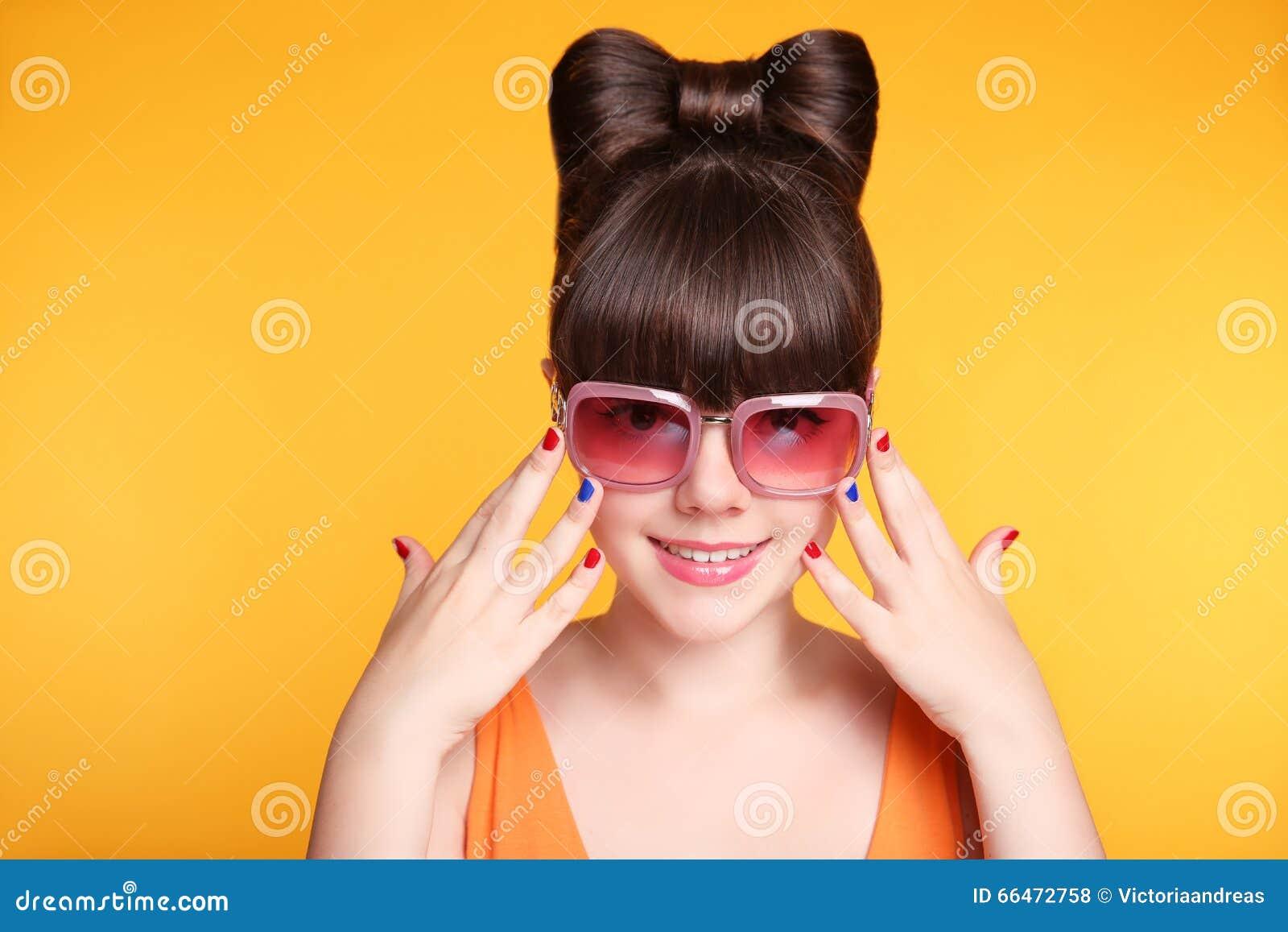 Glückliches lächelndes jugendlich Mädchen mit Modesonnenbrille, Bogenfrisur a