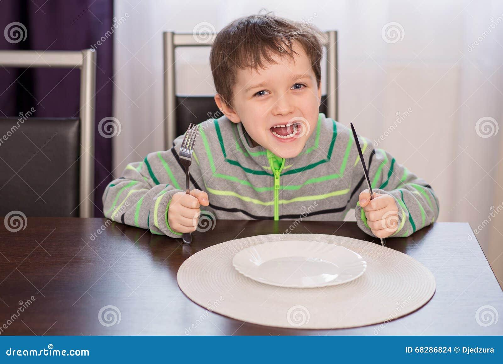 Glückliches lächelndes Jungenkinderwarteabendessen