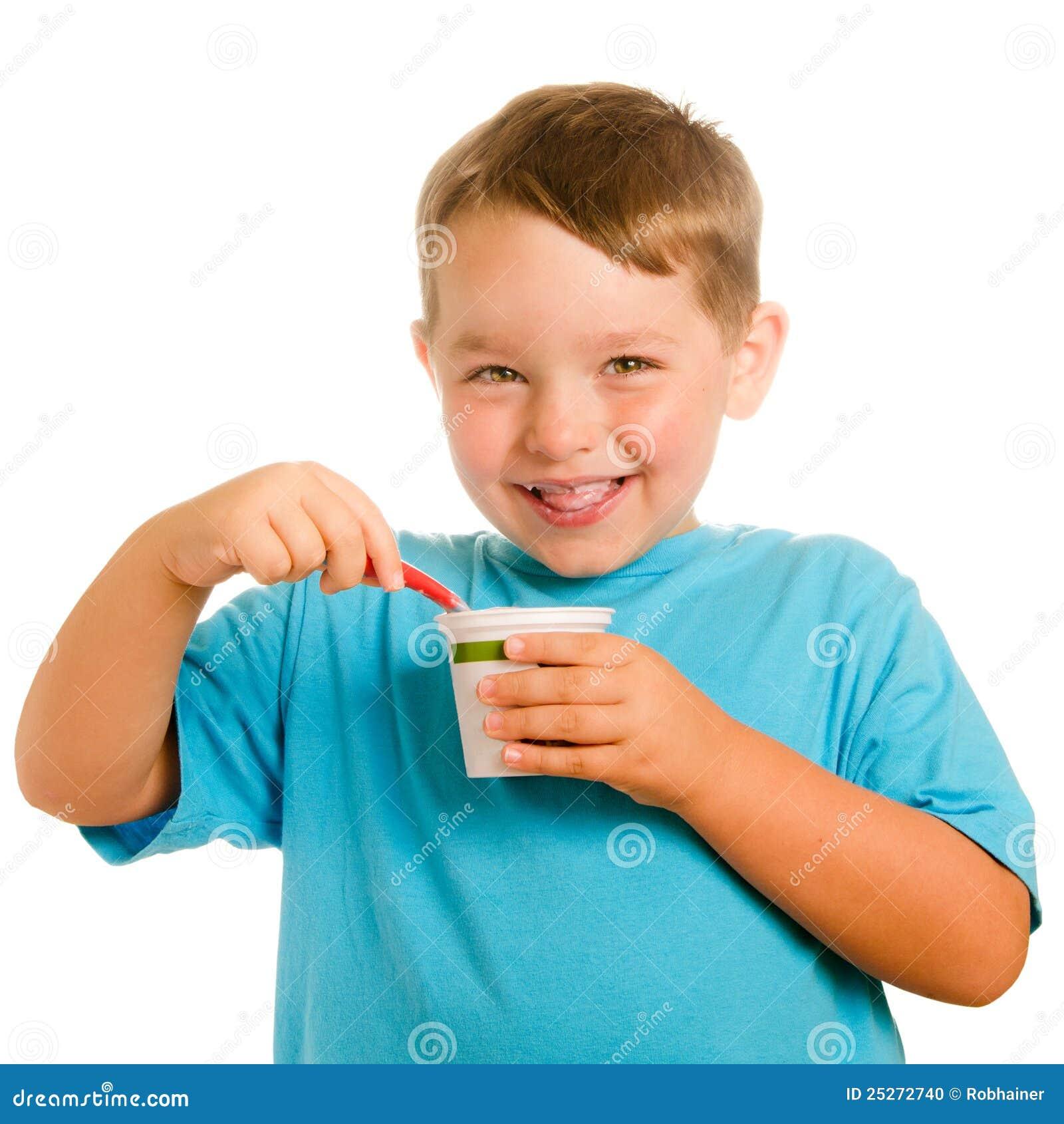 Glückliches lächelndes junges Kind, das Joghurt isst