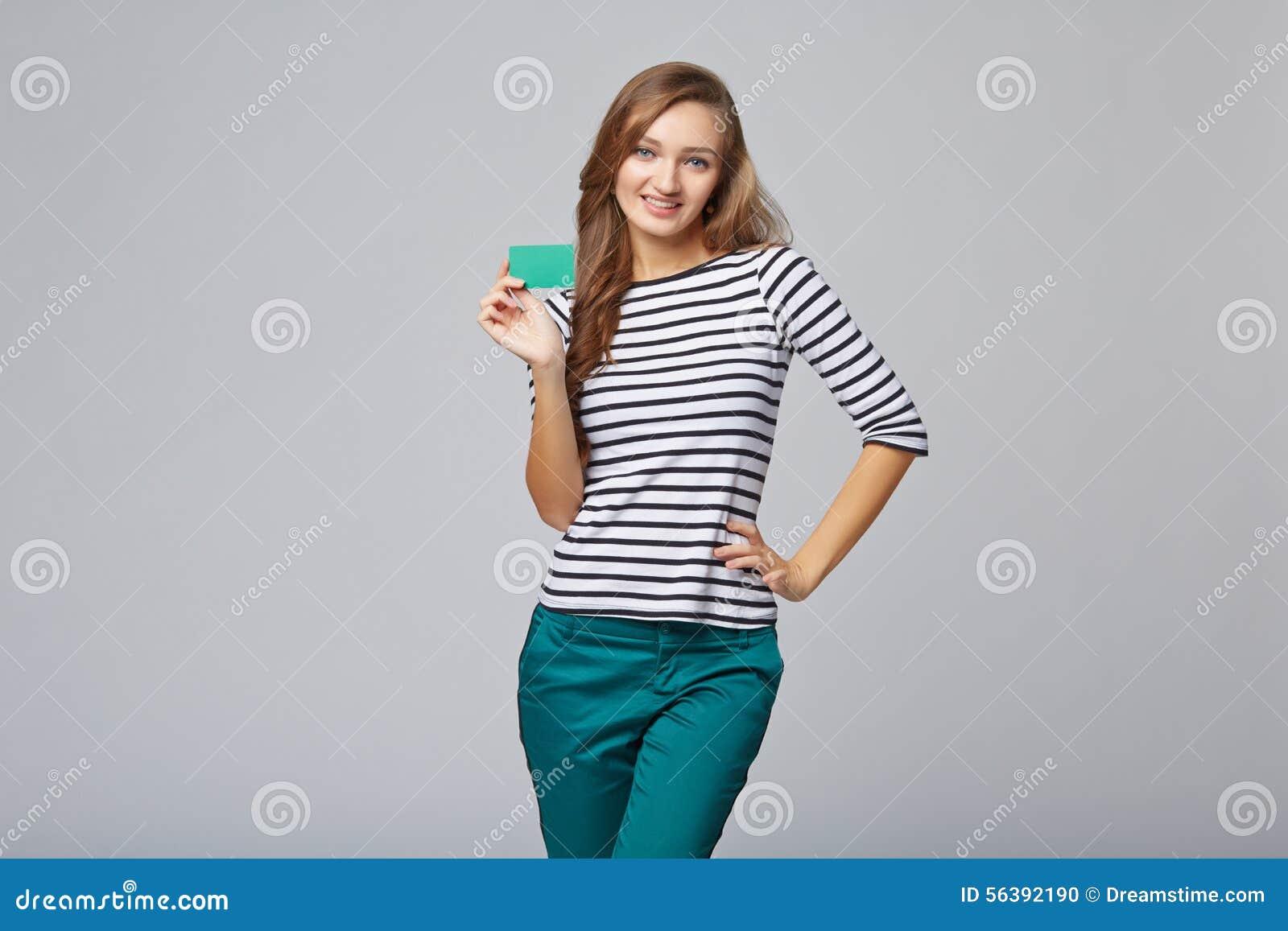 Glückliches lächelndes Mädchen in der Freizeitbekleidung, leere Kreditkarte zeigend