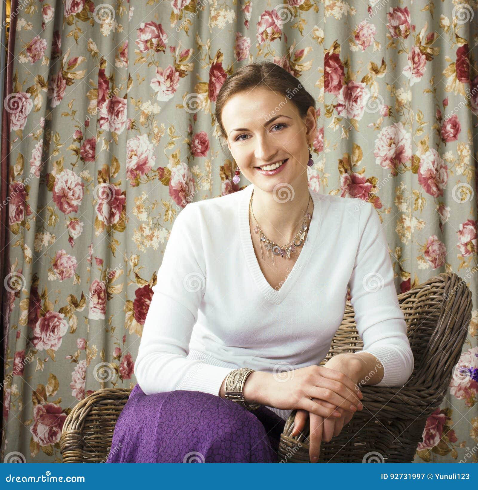 Glückliches lächelndes Sitzen der recht reifen Frau im Rauminnenraum, Leben