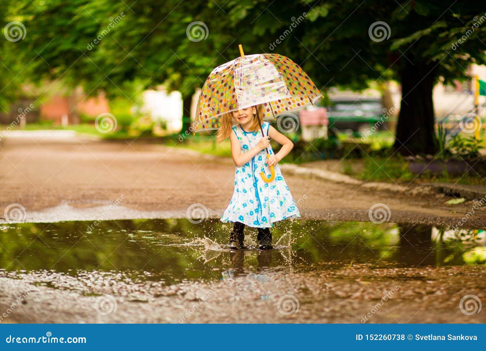 Glückliches lustiges Kindermädchen mit dem Regenschirm, der auf Pfützen in den Gummistiefeln und im Kleid und im Lachen springt