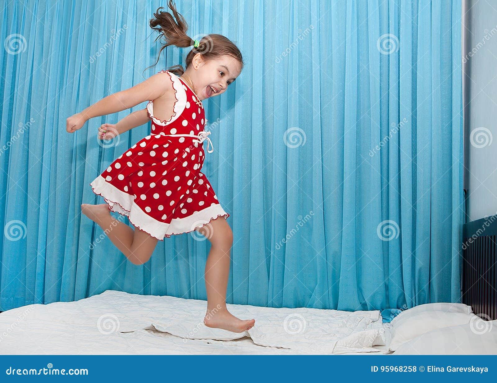 Glückliches Mädchen, das auf das Bett springt