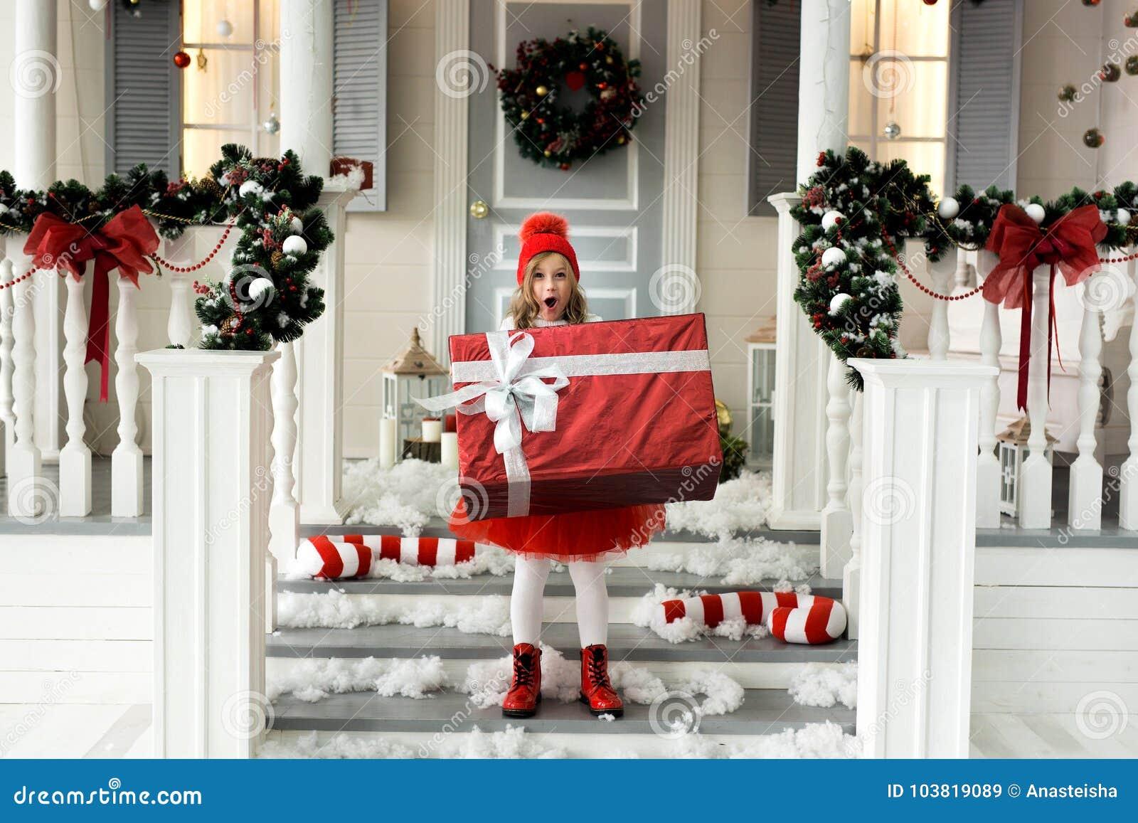 Glückliches Mädchen, das einen großen Kasten mit einem Geschenk hält Weihnachts- und Leutekonzept