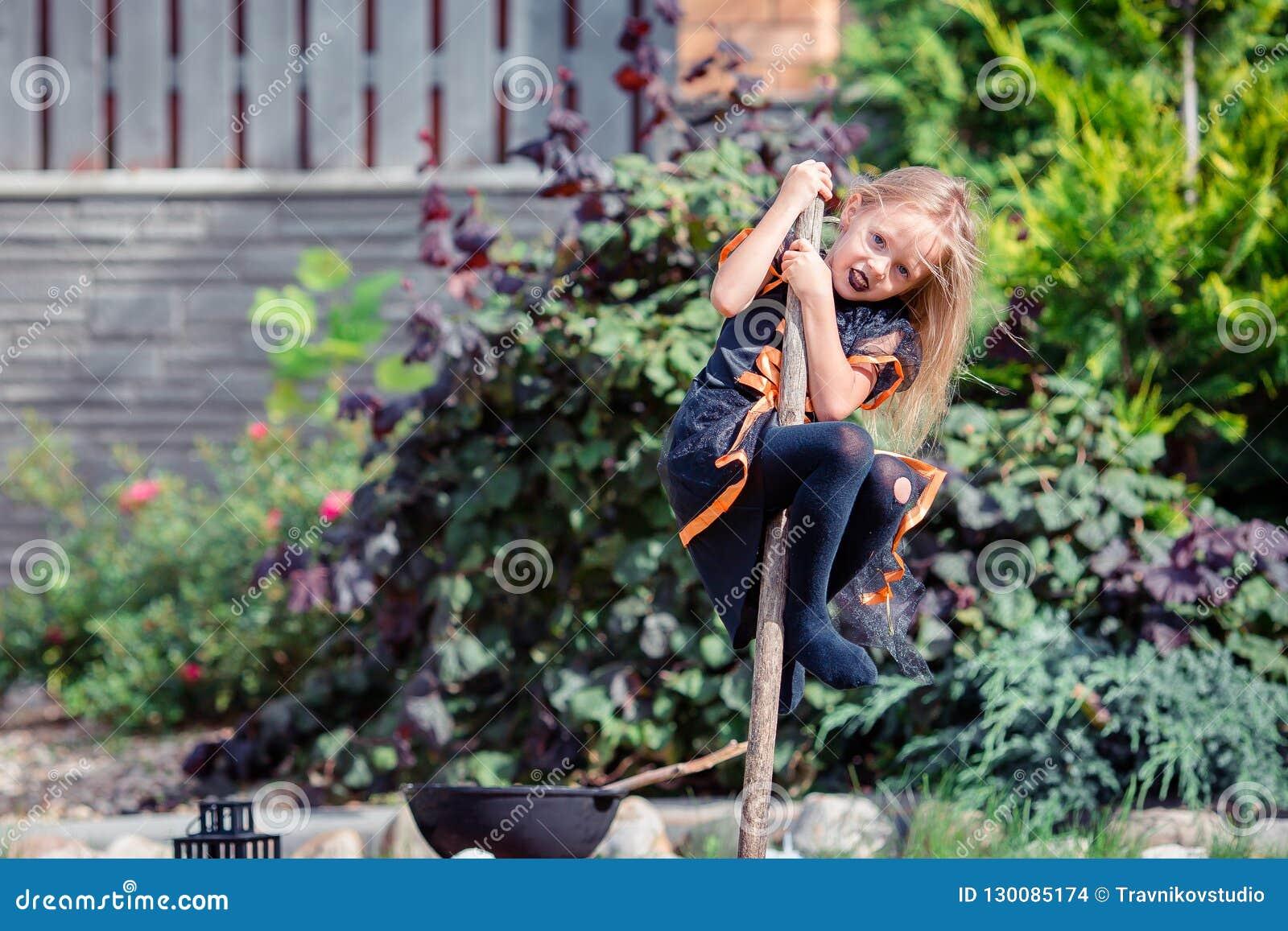 Glückliches Mädchen in Halloween-Kostüm mit Steckfassungskürbis Trick oder Festlichkeit