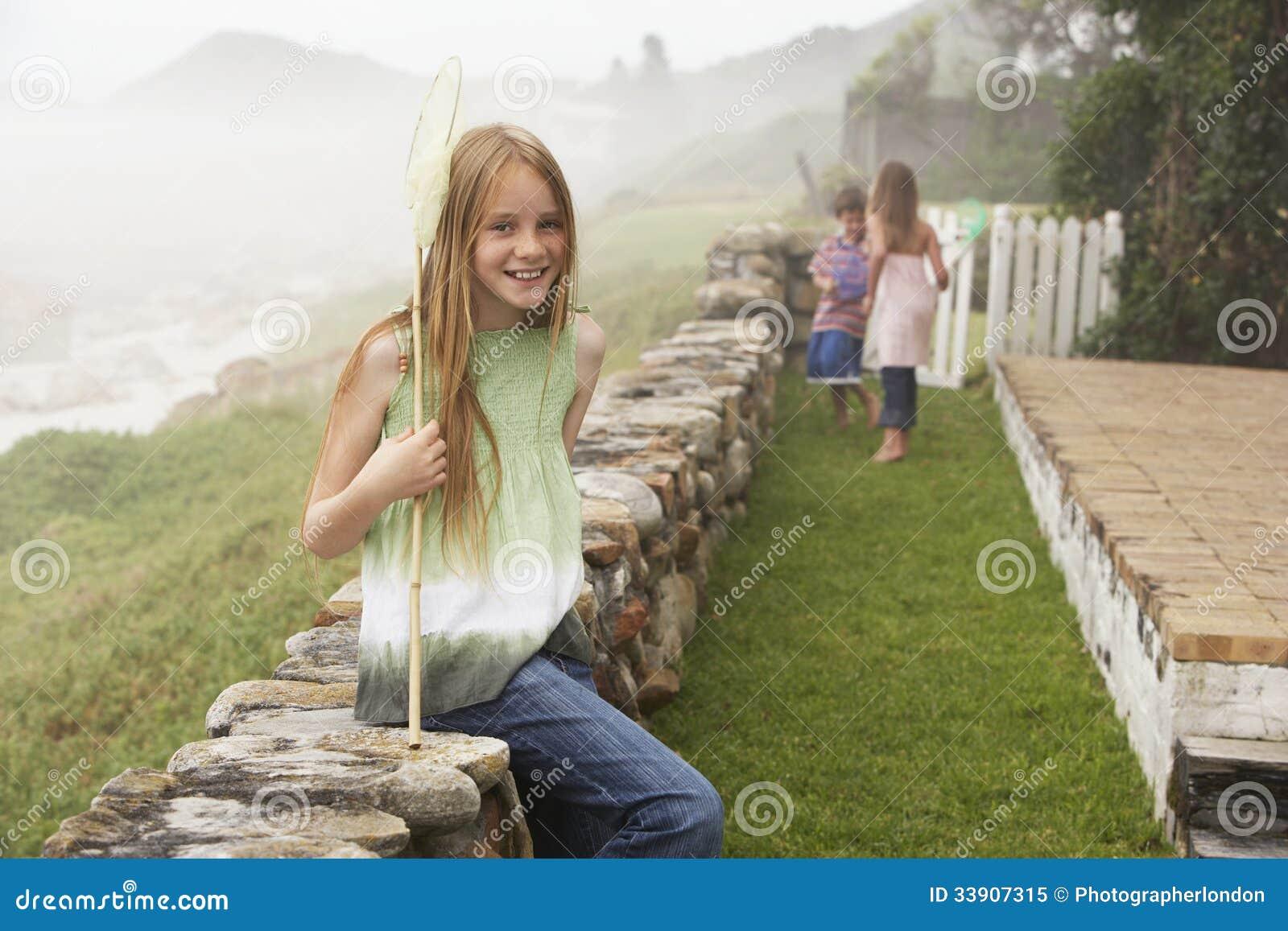 Glückliches Mädchen mit dem Fischernetz, das auf Steinwand am Yard sitzt