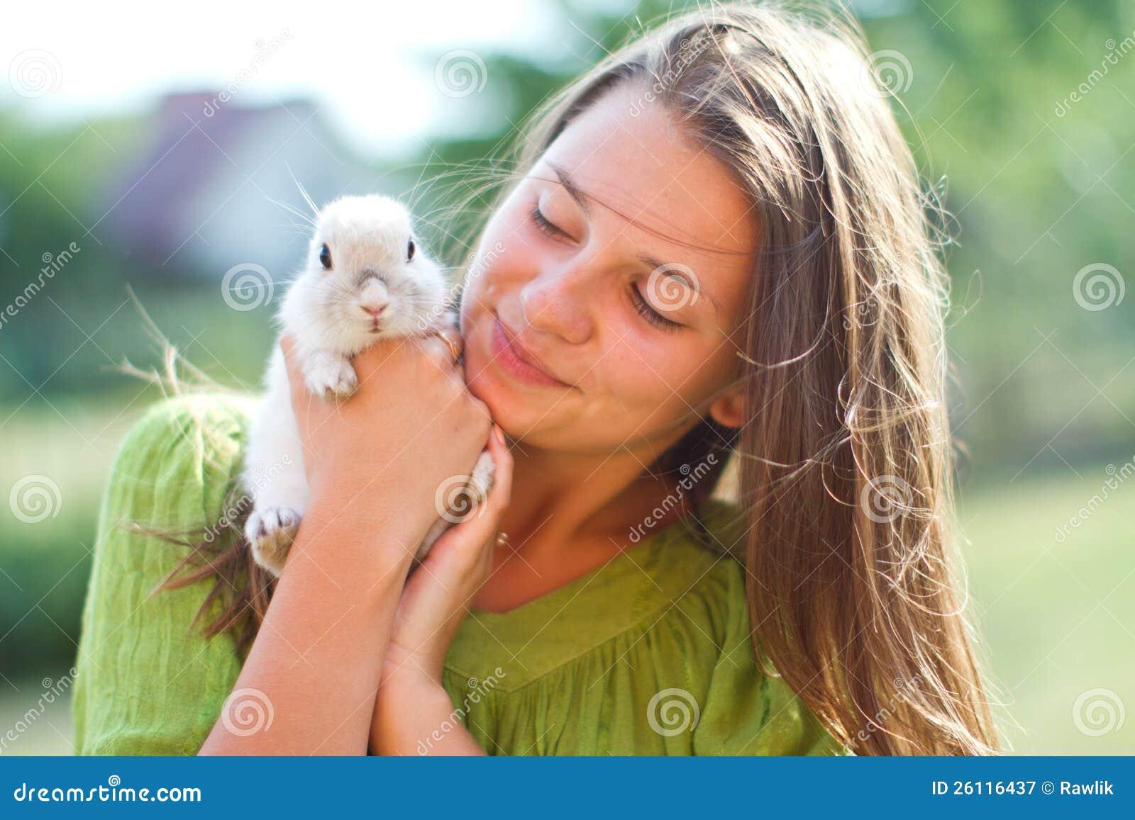 Glückliches Mädchen mit einem Kaninchen in ihren Armen