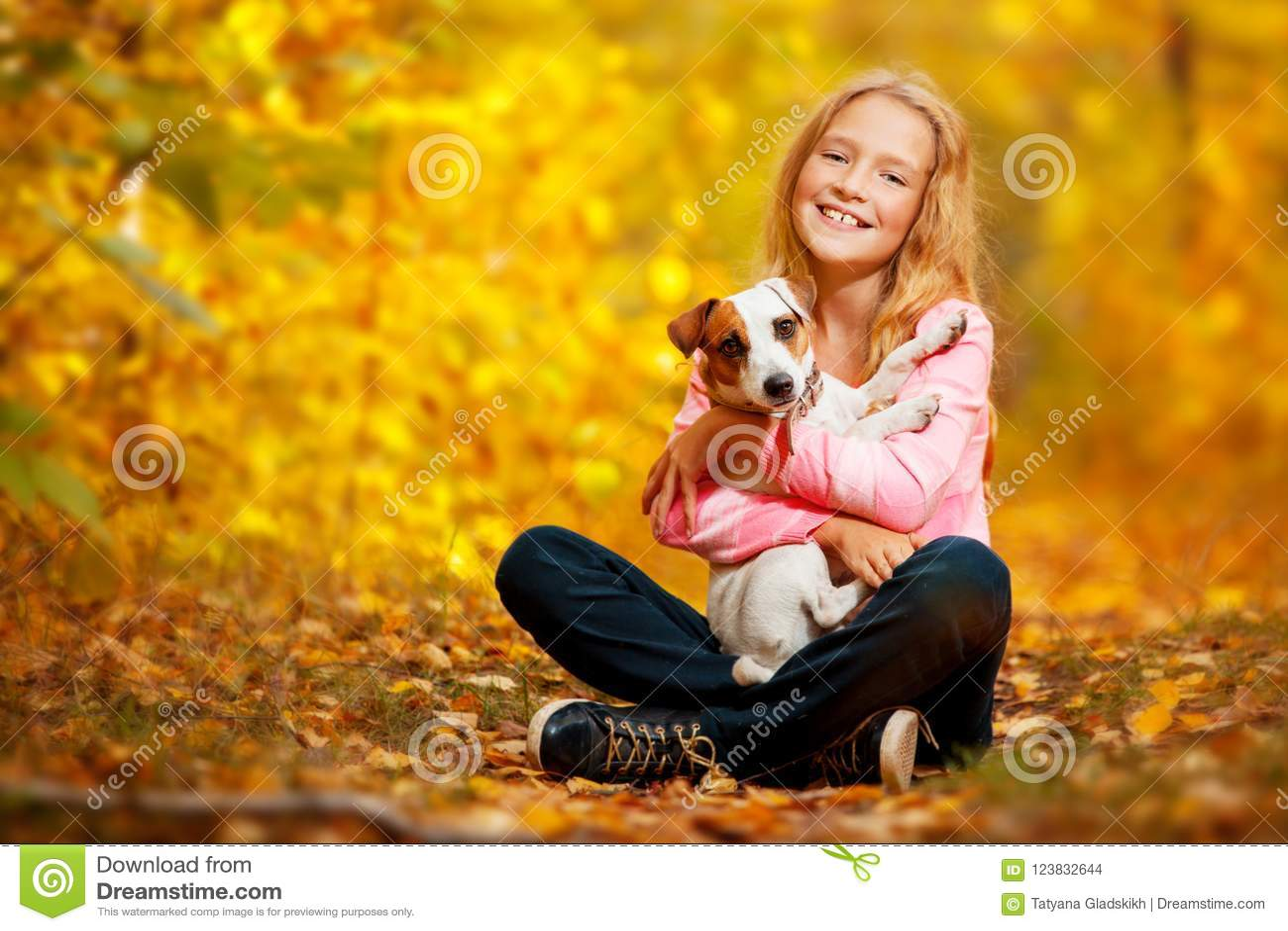 Glückliches Mädchen mit Hund am Herbst