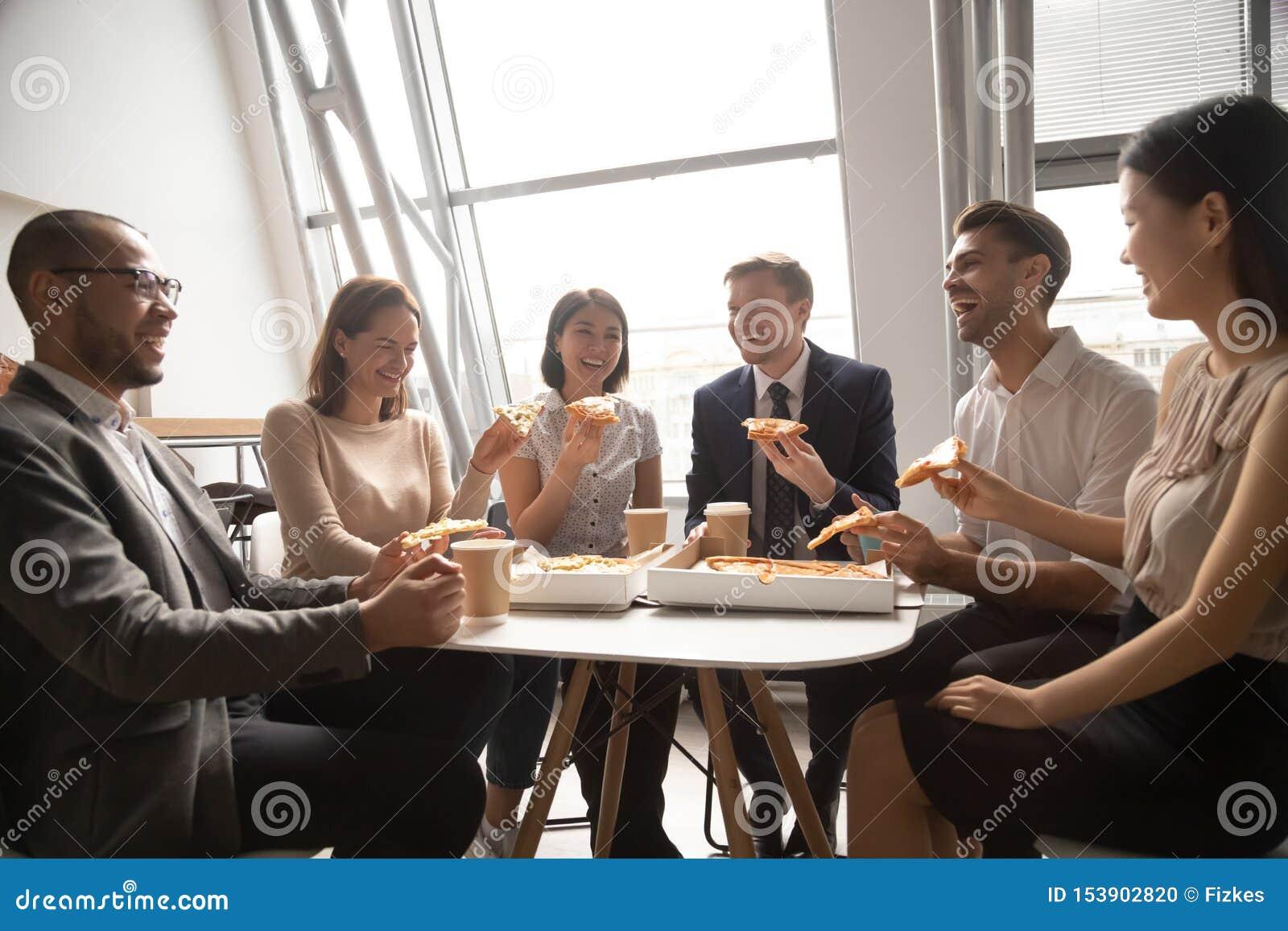 Glückliches multikulturelles Personalarbeitskraft-Geschäftsteam, das den Spaß isst Pizza hat