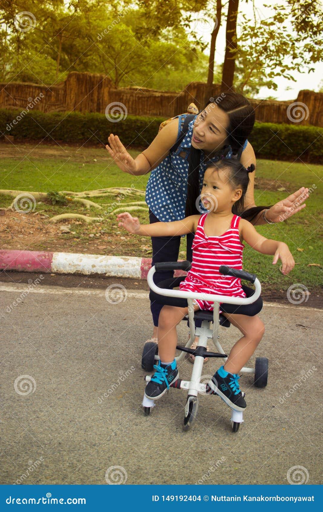 Gl?ckliches Mutterspiel mit ihrem Kind beim Druck eines Spazierg?ngers im Park