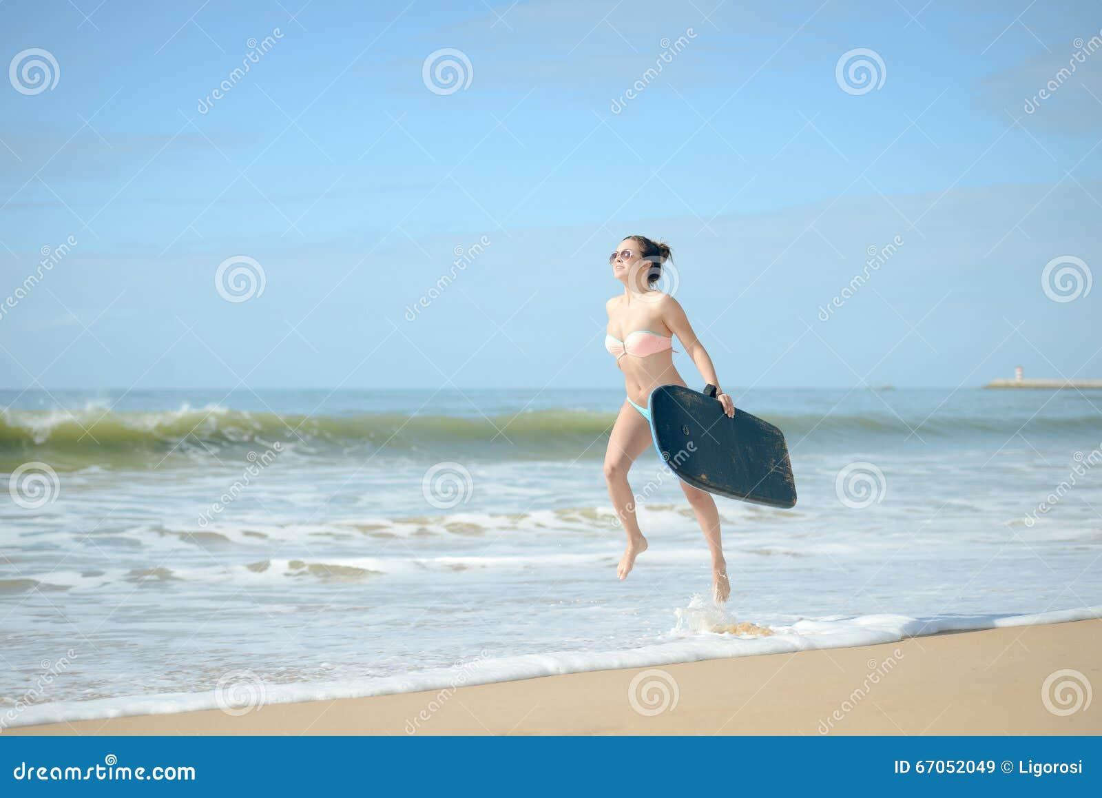 Glückliches nettes gehendes Surfen des frohen Surfermädchens am Ozeanstrand, der in Wasser läuft Weibliche Bikinifrauenüberschrif