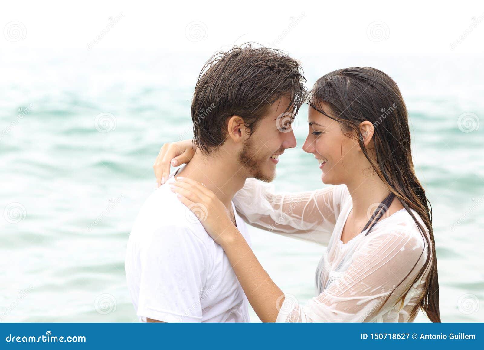 Glückliches Paar bereit, das Baden auf dem Strand zu küssen