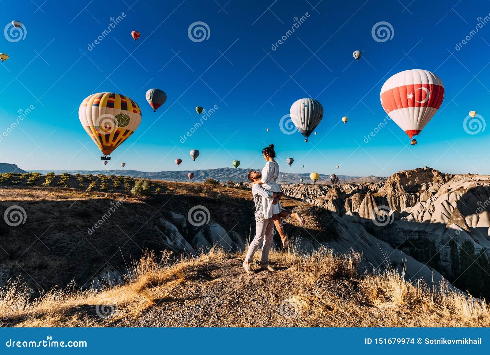 Glückliches Paar in Cappadocia Der Mann schlug zum Mädchen vor Flitterwochen in Cappadocia Verbinden Sie am Ballonfestival Verbin