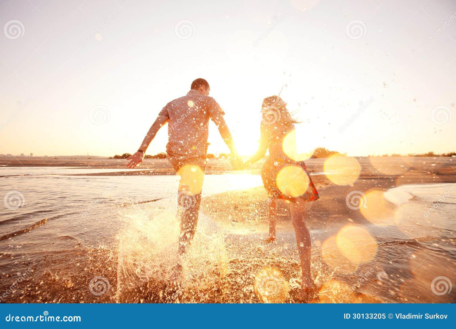 Paare, die auf den Strand laufen