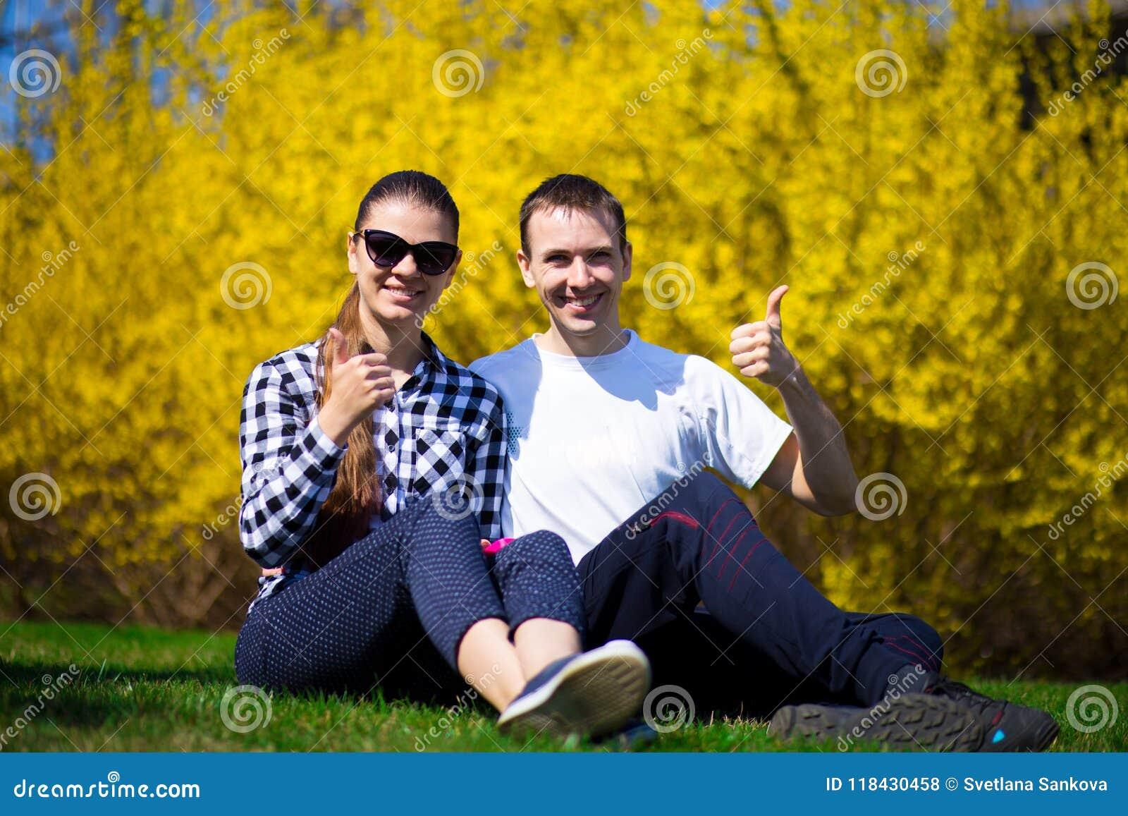 Glückliches Paar, das auf frischem Gras im Park umarmt