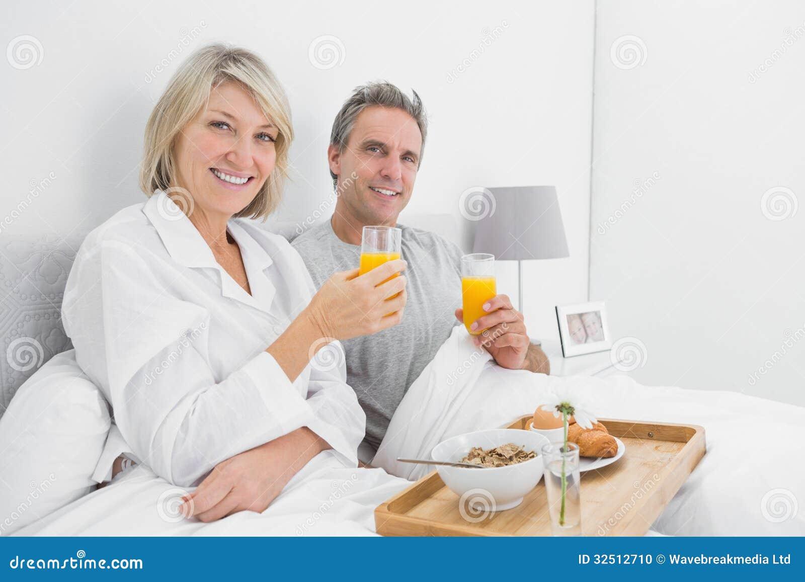 gl ckliches paar das orangensaft am fr hst ck im bett isst stockfoto bild 32512710. Black Bedroom Furniture Sets. Home Design Ideas