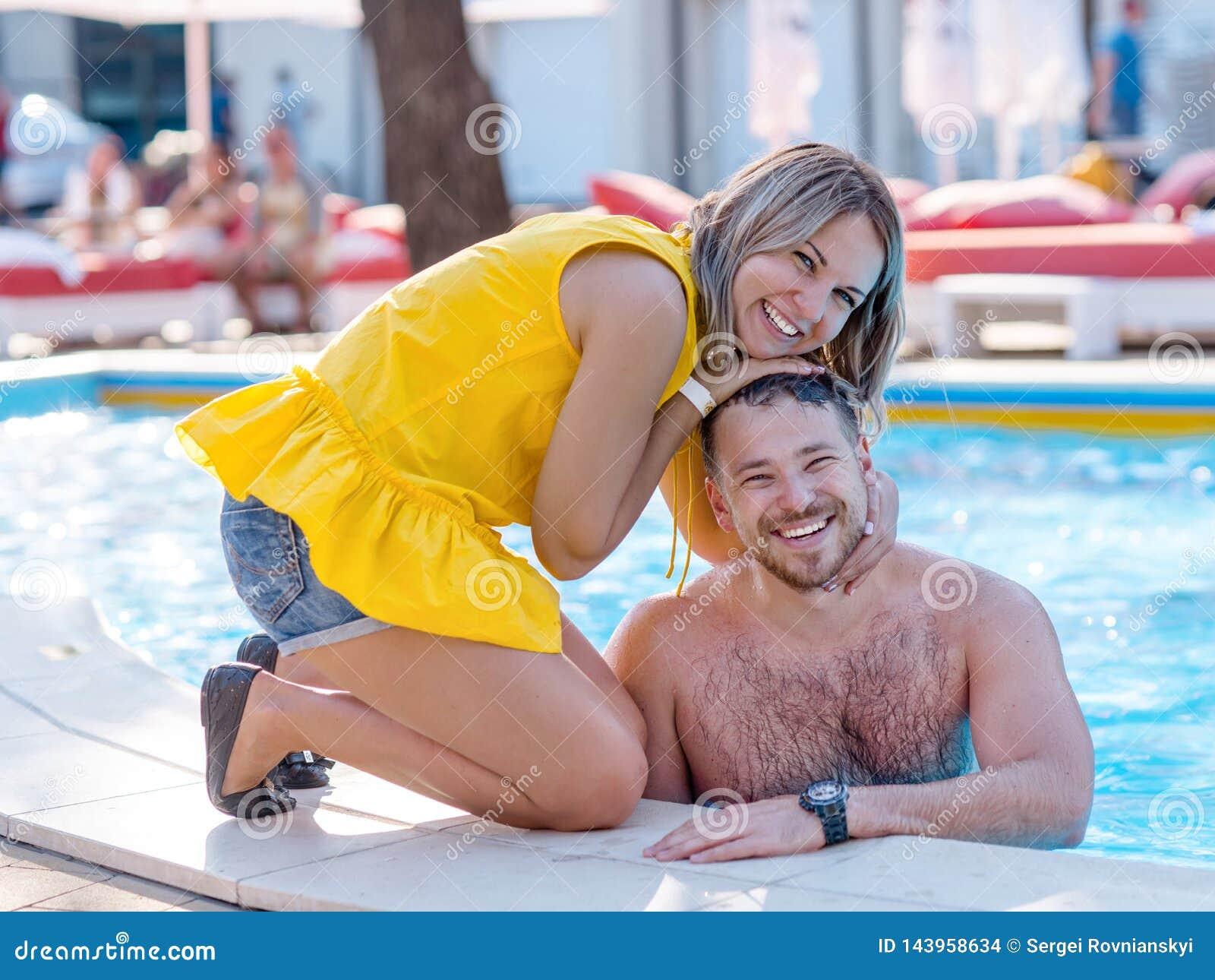 Glückliches Paar, das Sommerzeit n ein FerienzentrumSwimmingpool genießt