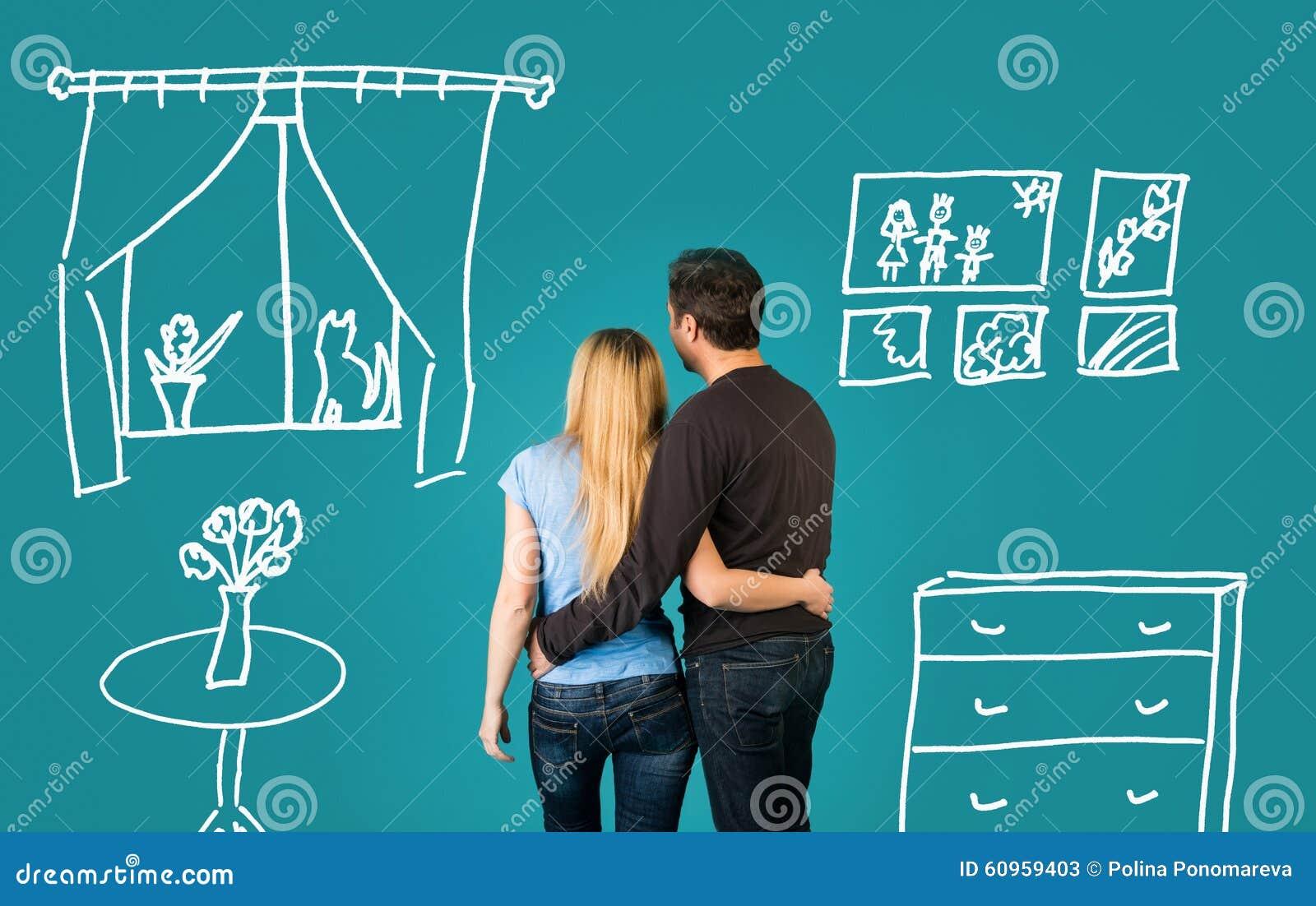 Glückliches Paar, das von ihrem neuen Haus träumt und auf blauem Hintergrund versorgt