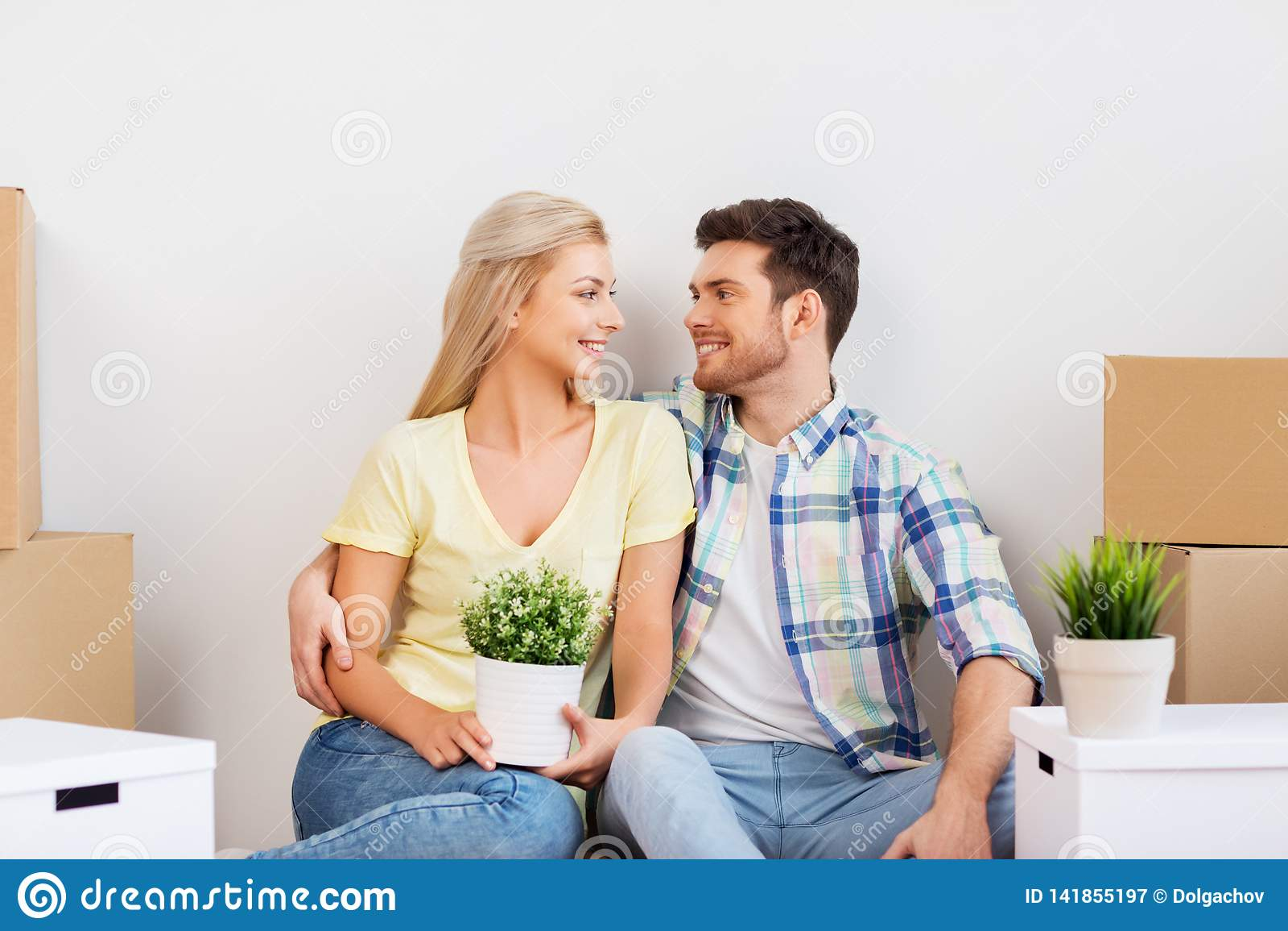 Glückliches Paar mit den Kästen, die auf neues Haus sich bewegen