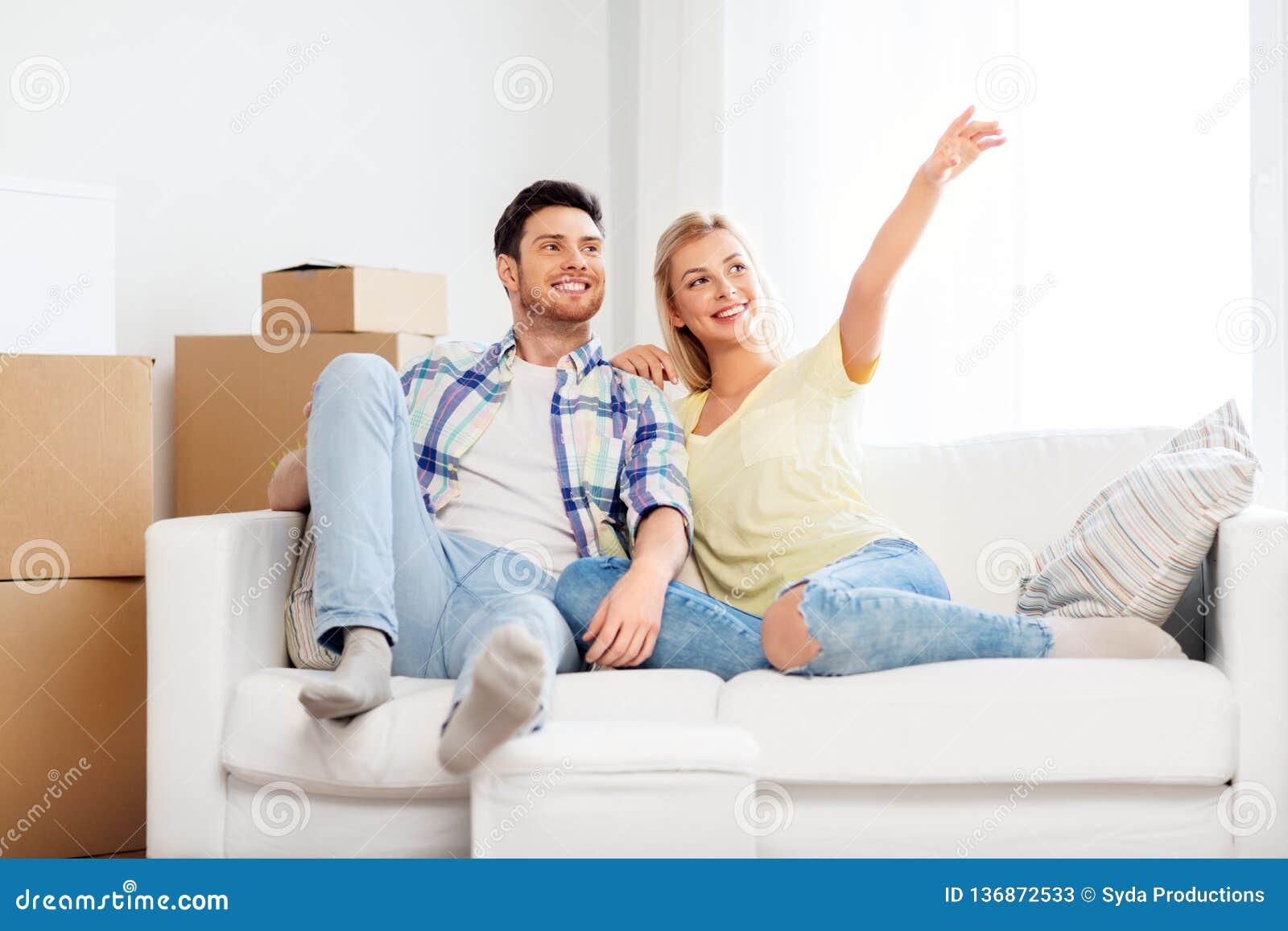 Glückliches Paar mit Pappschachteln am neuen Haus