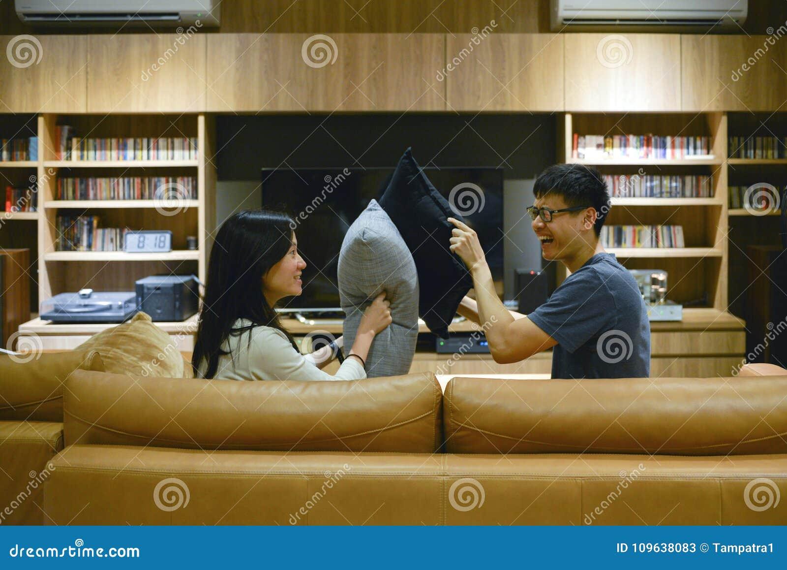Glückliches Paar schlug sich mit Kissen im Wohnzimmer nachts