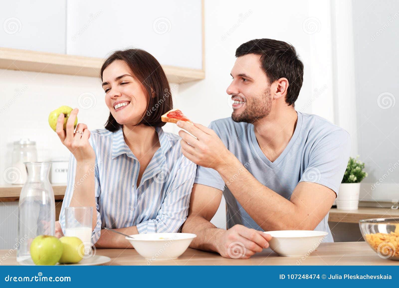 Glückliches Paar verbringen Freizeit, oder Wochenende zusammen an der Küche, schlägt froher Ehemann Frau vor, um Snack zu essen,