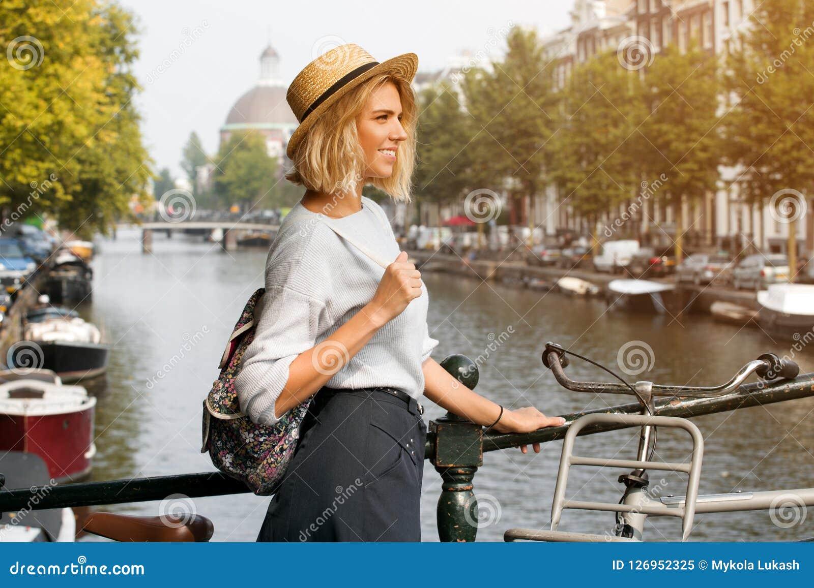 Glückliches Reisendmädchen, das Amsterdam-Stadt genießt Lächelnde Frau, die zur Seite auf Amsterdam-Kanal, die Niederlande, Europ