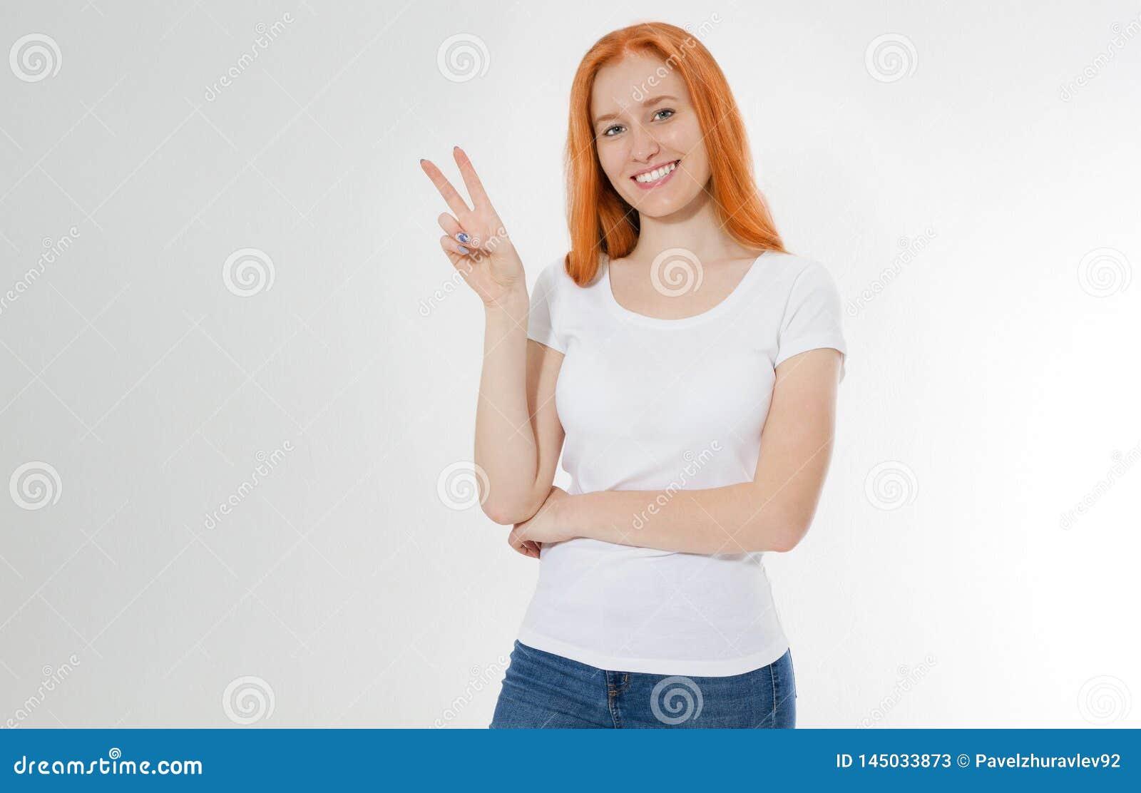 Glückliches rotes Haarmädchen, das Kamera mit Lächeln betrachtet und Friedenszeichen mit den Fingern, junger Rothaarigefrau ü