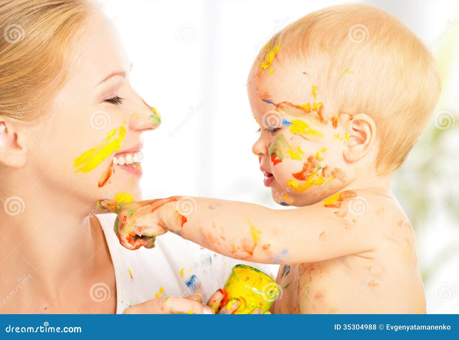 Glückliches schmutziges Baby zeichnet Farben auf ihrem Gesicht der Mutter