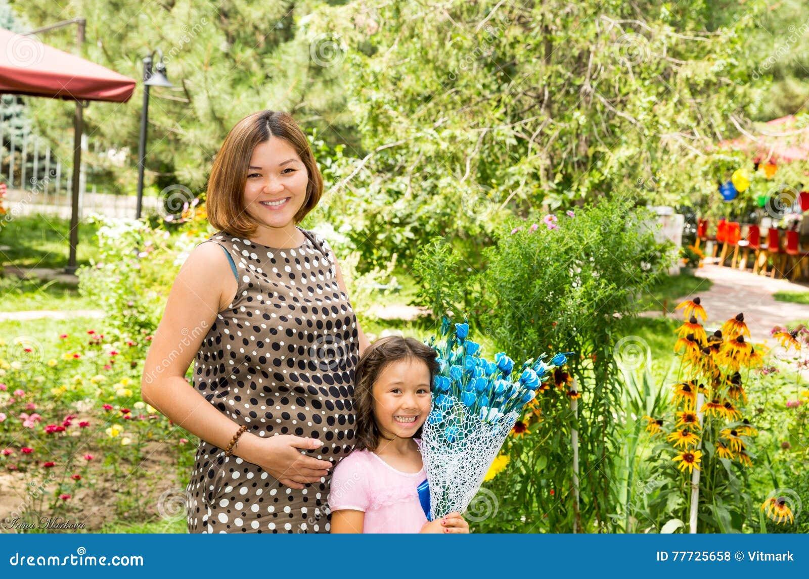 Glückliches schwangeres asiatisches Mutter- und Kindermädchenumarmen Das Konzept der Kindheit und der Familie