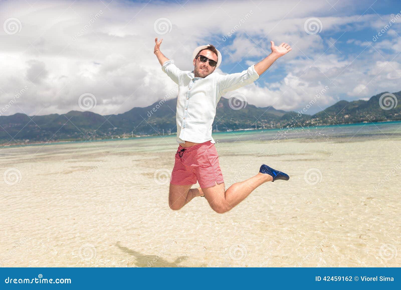 Glückliches Springen des jungen Mannes der Freude auf dem Strand
