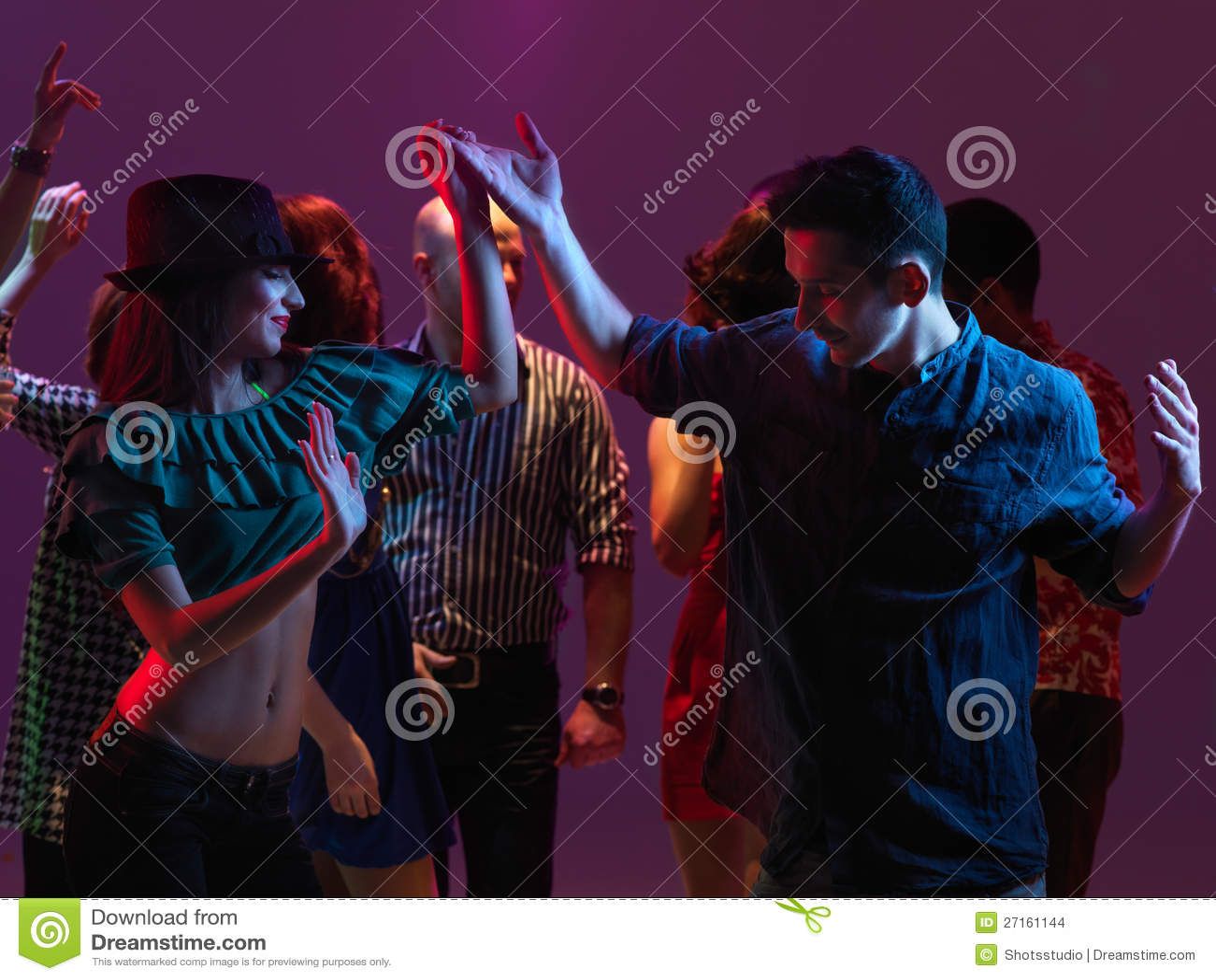 Glückliches Tanzen der jungen Leute im Nachtclub