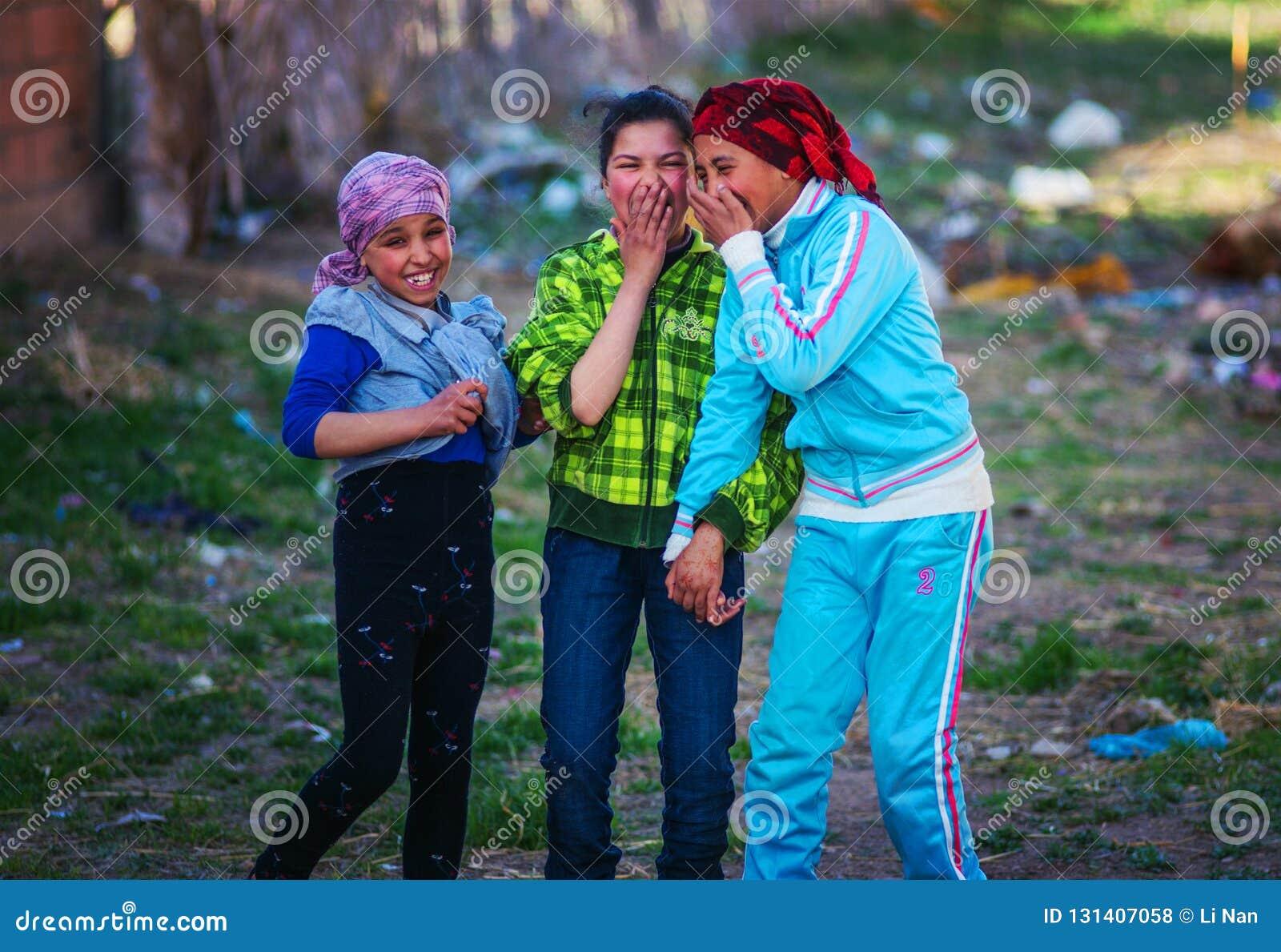 Glückliches und buntes Islammädchen mit altem traditionellem Musselinkleid in Marokko-Dorf