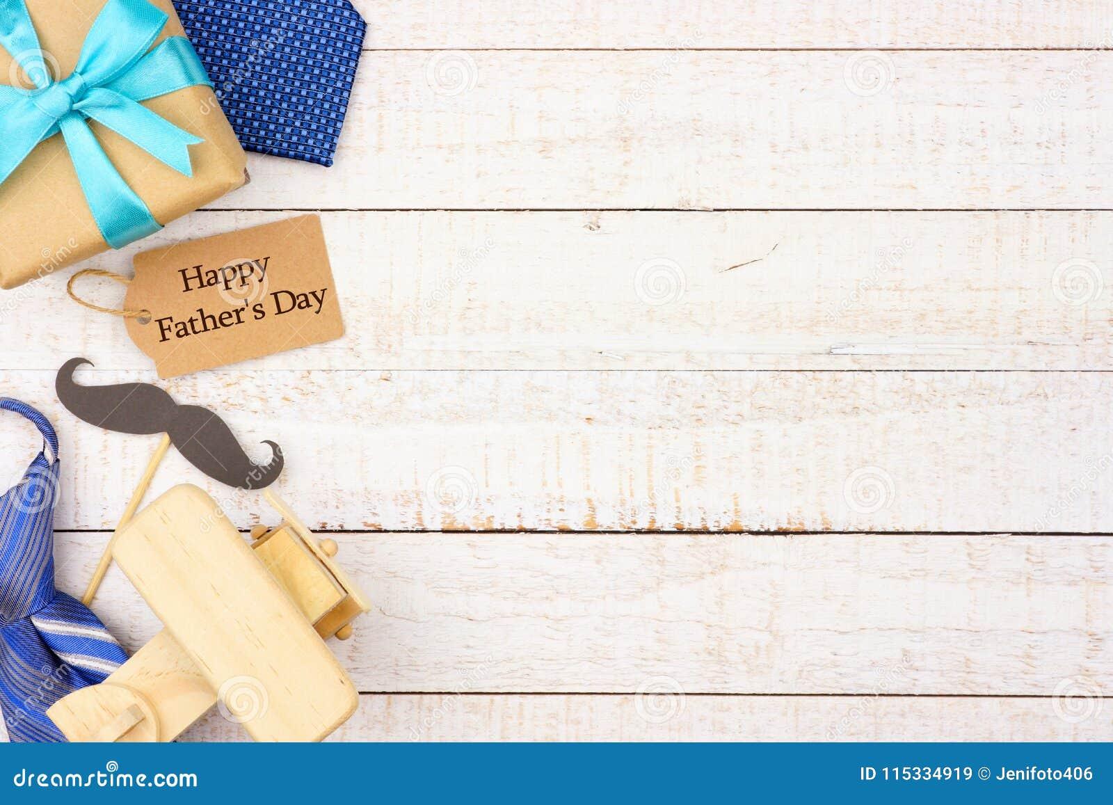 Glückliches Vatertags-Geschenktag mit Seitengrenze von Geschenken, von Bindungen und von Dekor auf weißem Holz