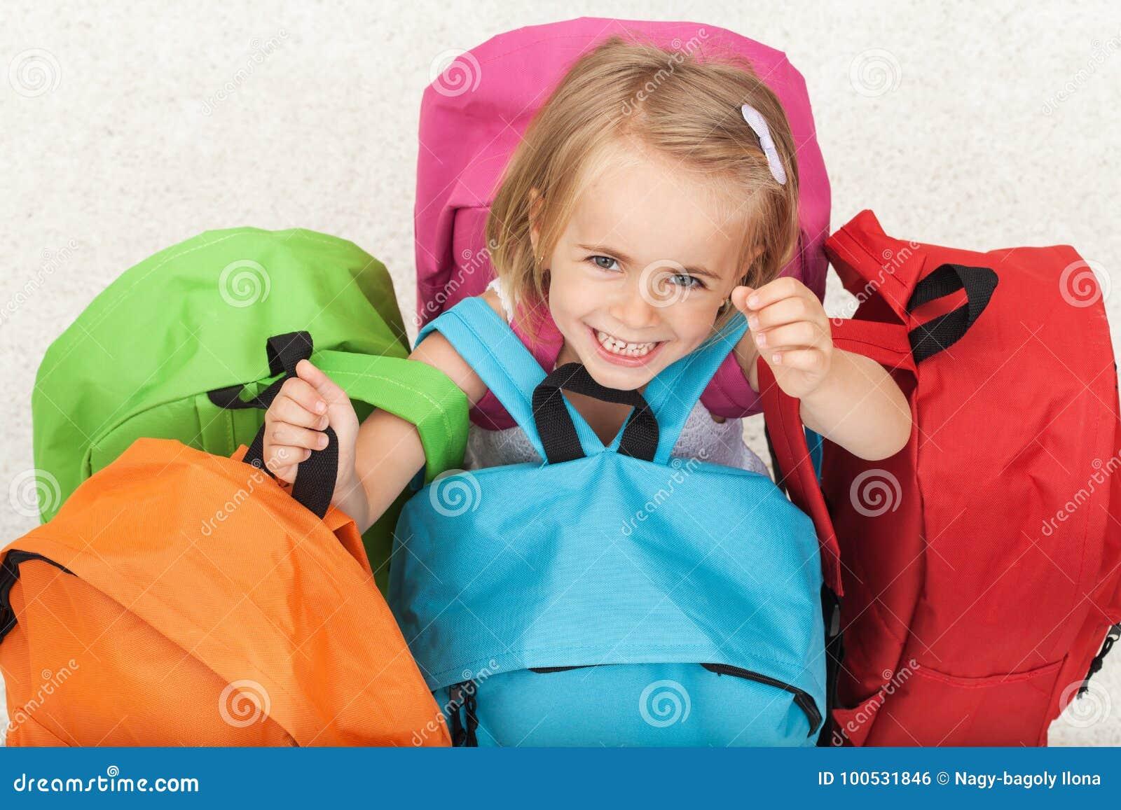 Glückliches Vorschülermädchen, das ihre Schultasche von einem bunten s wählt