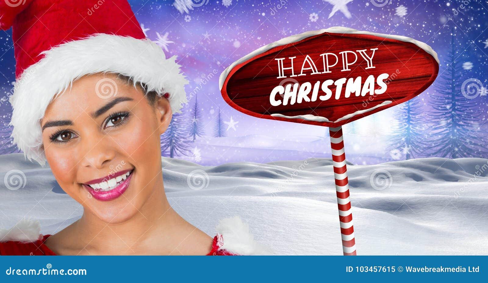 Glückliches Weihnachtstext und -Santa Wooden Wegweiser in der Weihnachtswinterlandschaft
