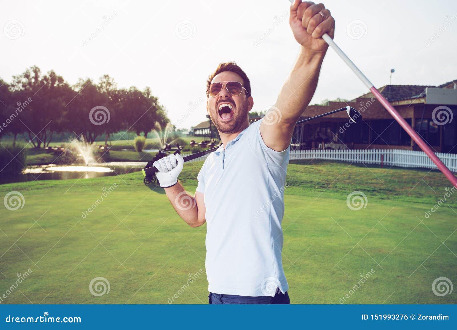 Glücksieger-Manngolfspieler, der herein einen Golfball setzt, um zu durchlöchern