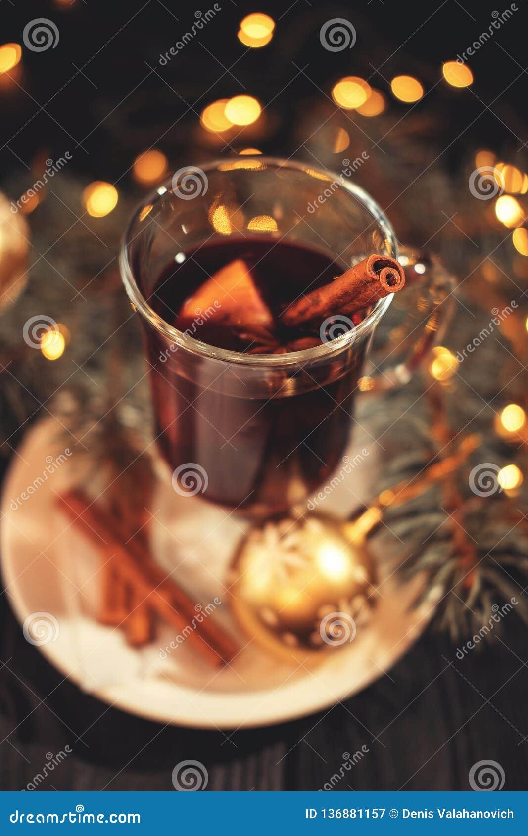 Glühwein auf weißer Platte auf schwarzem Holztisch, Zimtstangeweihnachtsball, Lichter