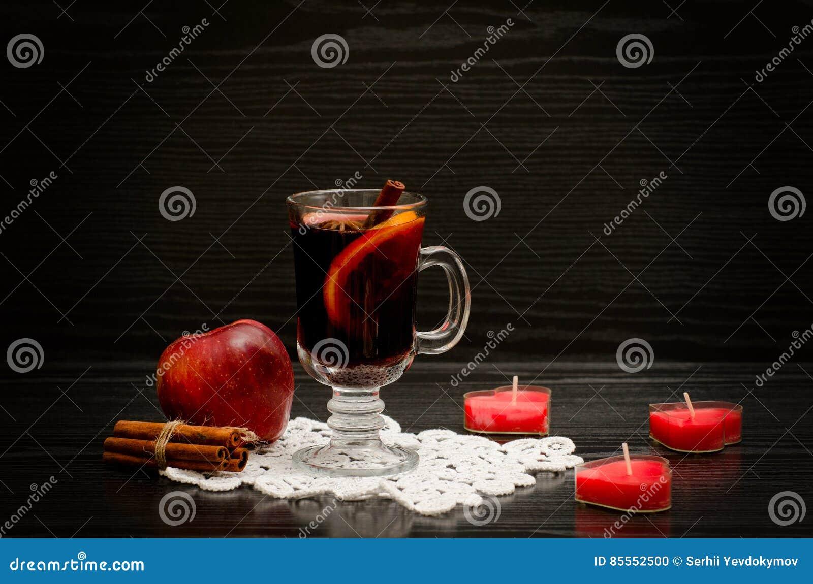 Glühwein mit Gewürzen auf einer Spitzeserviette Kerzen in Form eines Herzens, der Zimtstangen und des Apfels