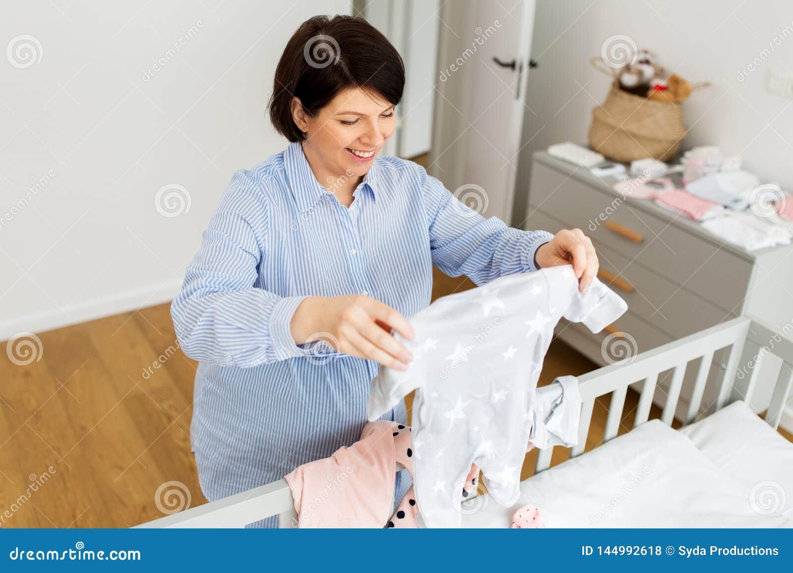 Gl?ckliche Einstellungsbabykleidung der schwangeren Frau zu Hause