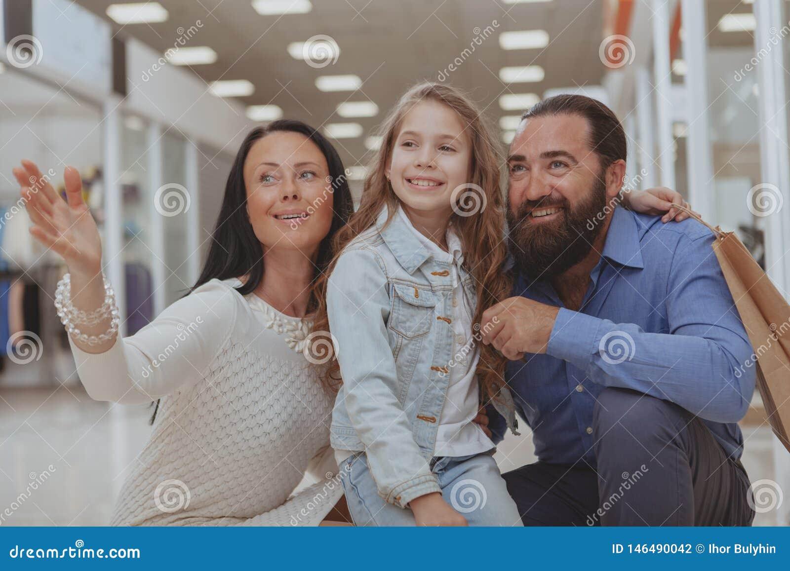 Gl?ckliche Familie, die im Einkaufszentrum zusammen kauft