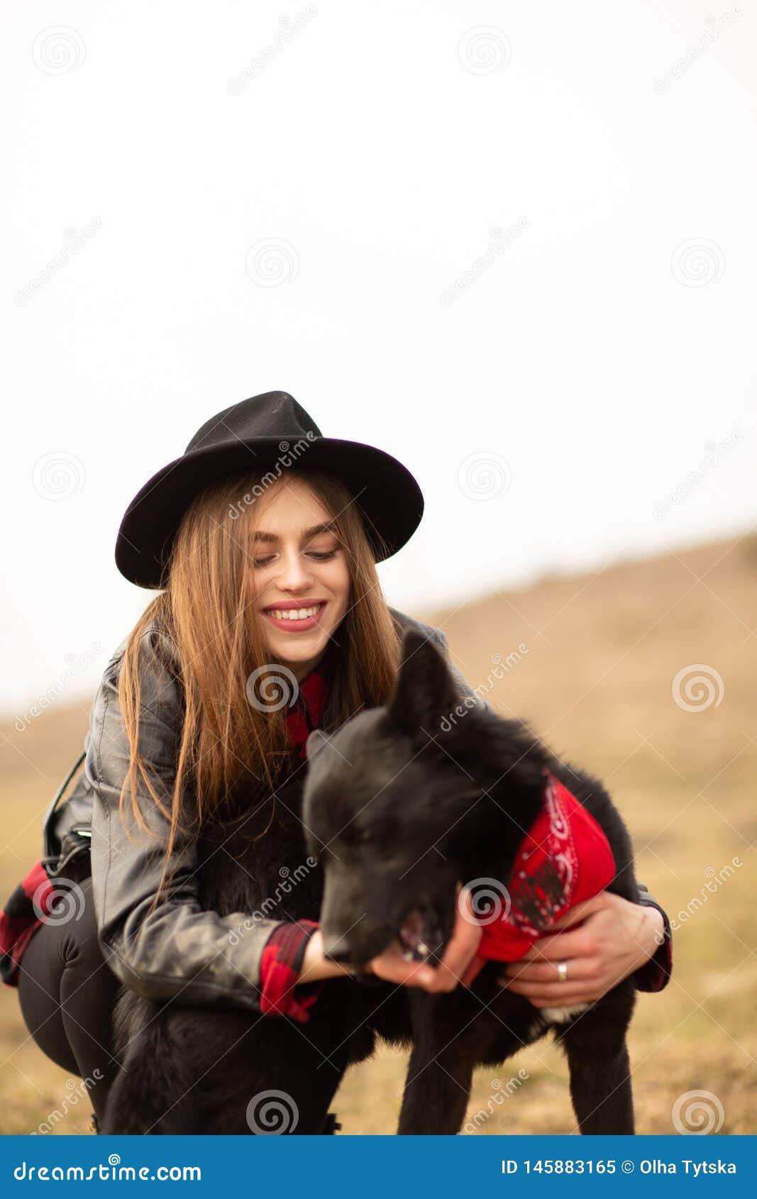Gl?ckliche junge Frau mit dem schwarzen Hut, plaing mit ihrem schwarzen Hund auf dem Ufer des Sees