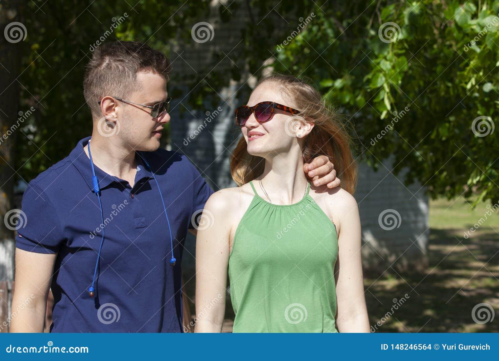 Gl?ckliche junge Paare, die drau?en umarmen und lachen