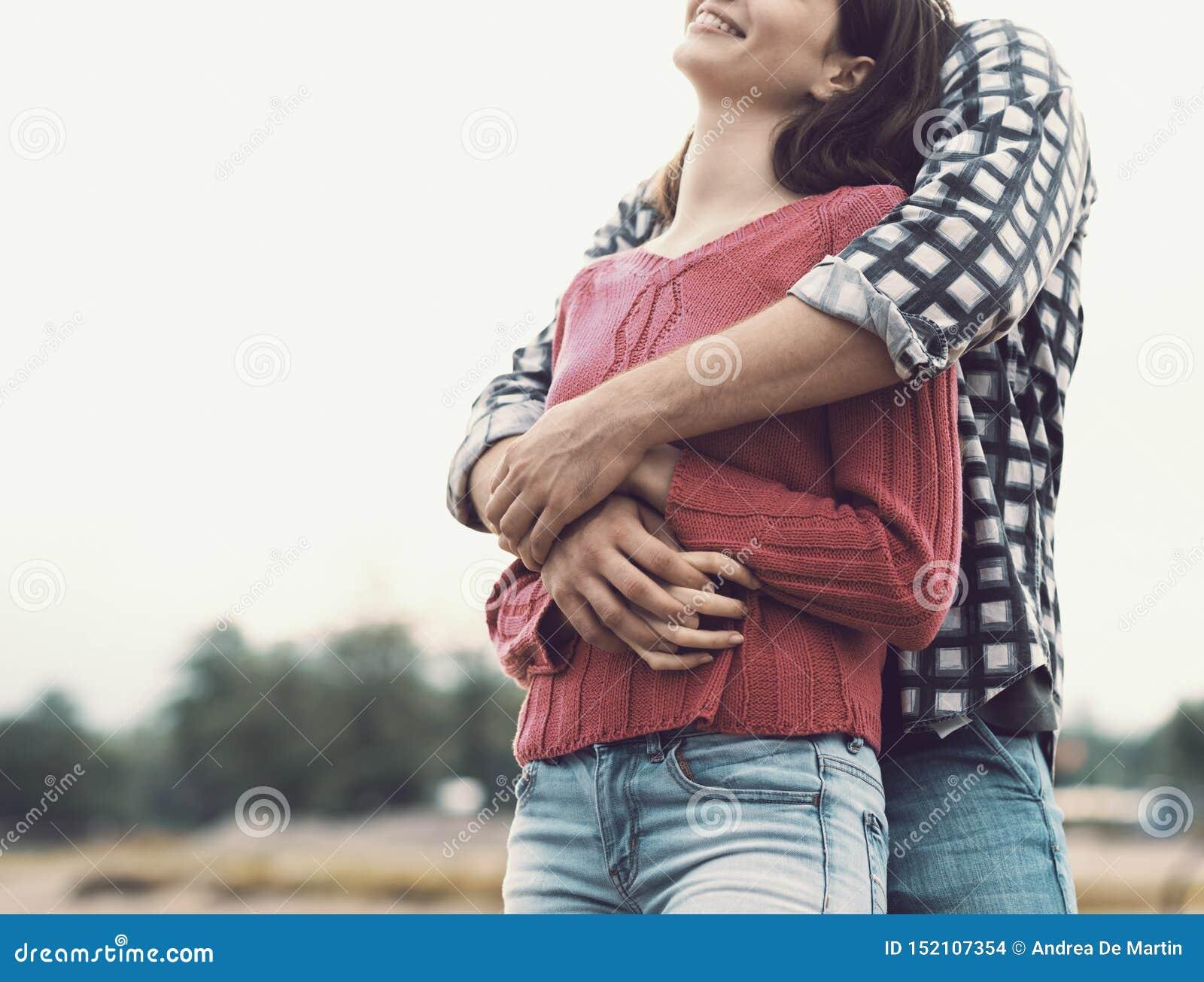 Gl?ckliche junge umarmende und l?chelnde Paare