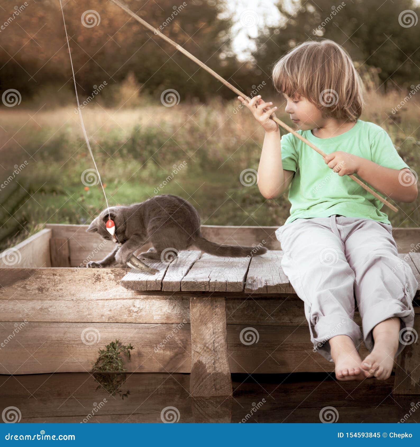Gl?cklicher Junge gehen, auf dem Fluss mit Haustier, Kindern eins und K?tzchen des Fischers mit einer Angelrute auf dem Ufer des