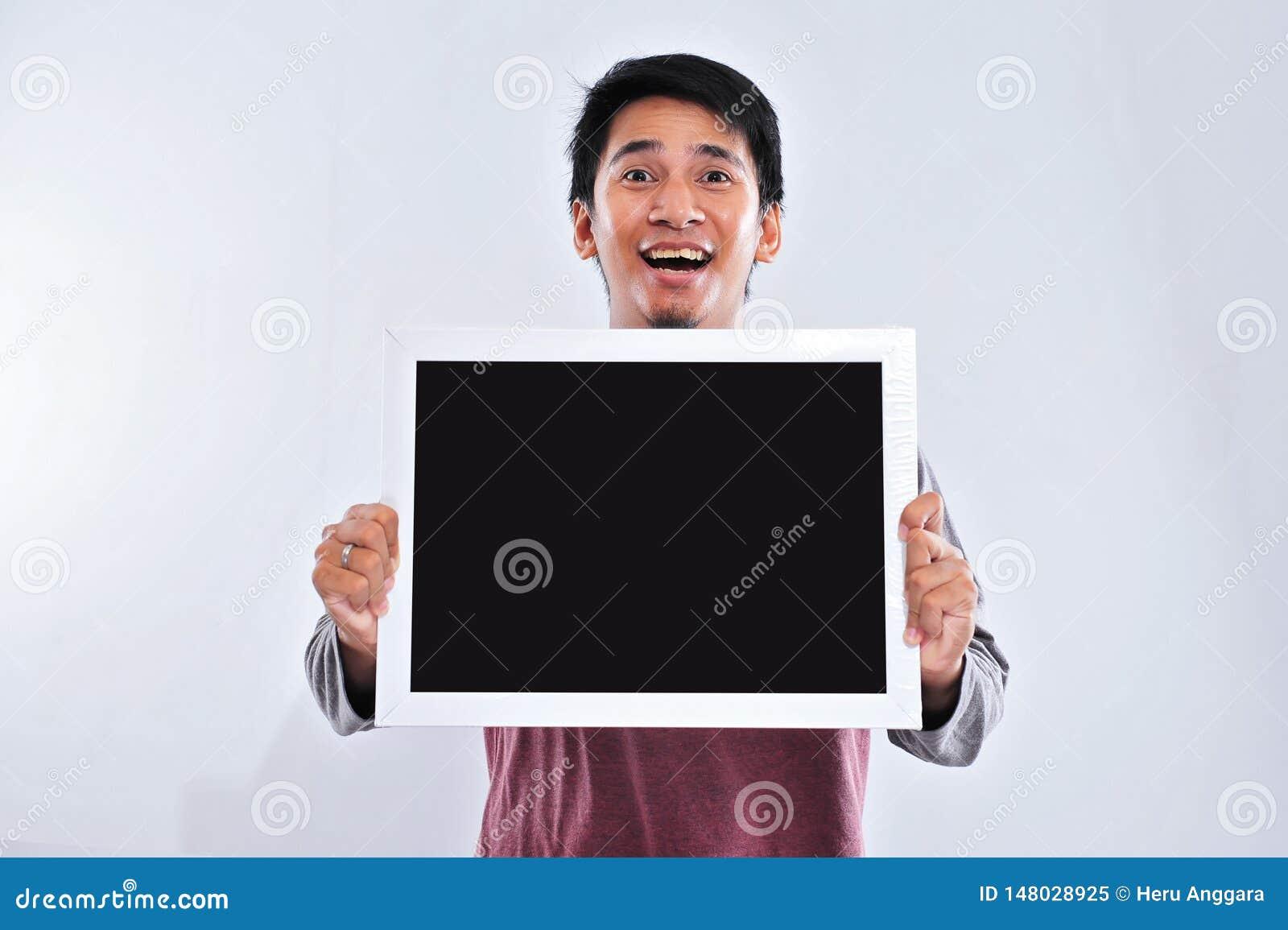 Gl?cklicher junger h?bscher asiatischer Mann, der die leere Tafel oder Brett bereit zu Ihrem Text h?lt und zeigt
