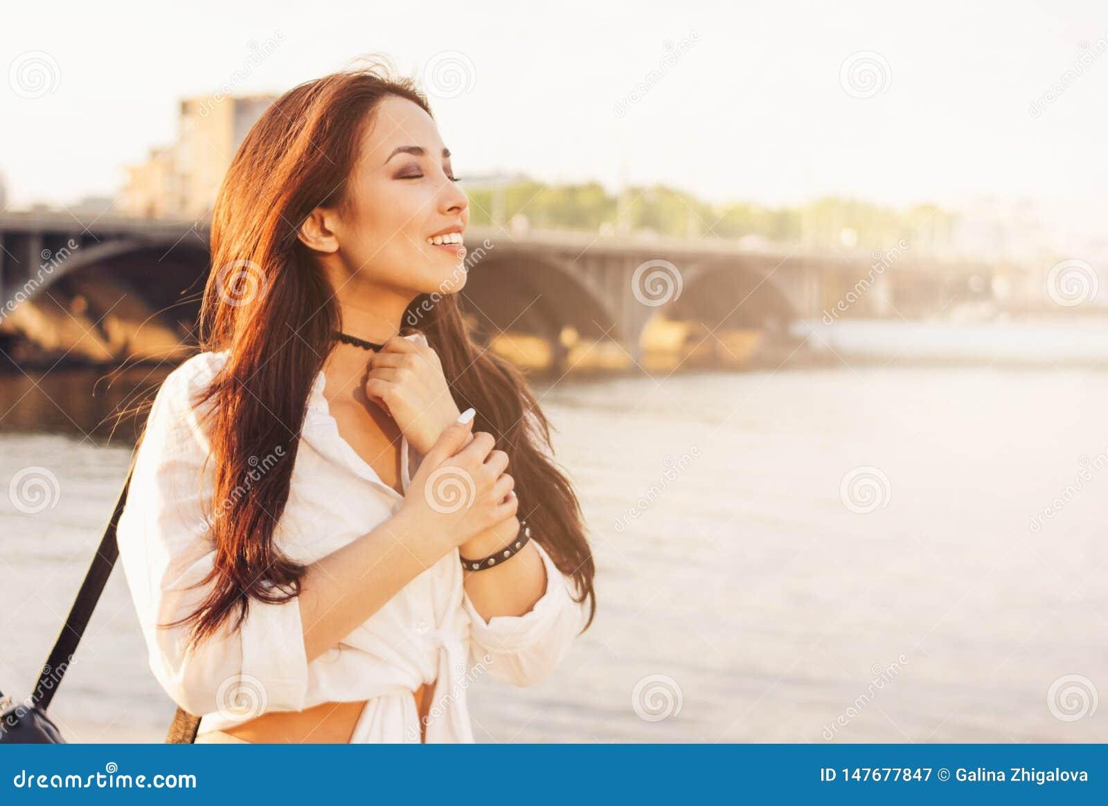 Gl?ckliches asiatisches M?dchen des positiven sch?nen langen Haares im wei?en Hemd auf Stadtfluss-Br?ckenhintergrund, Sommerreise