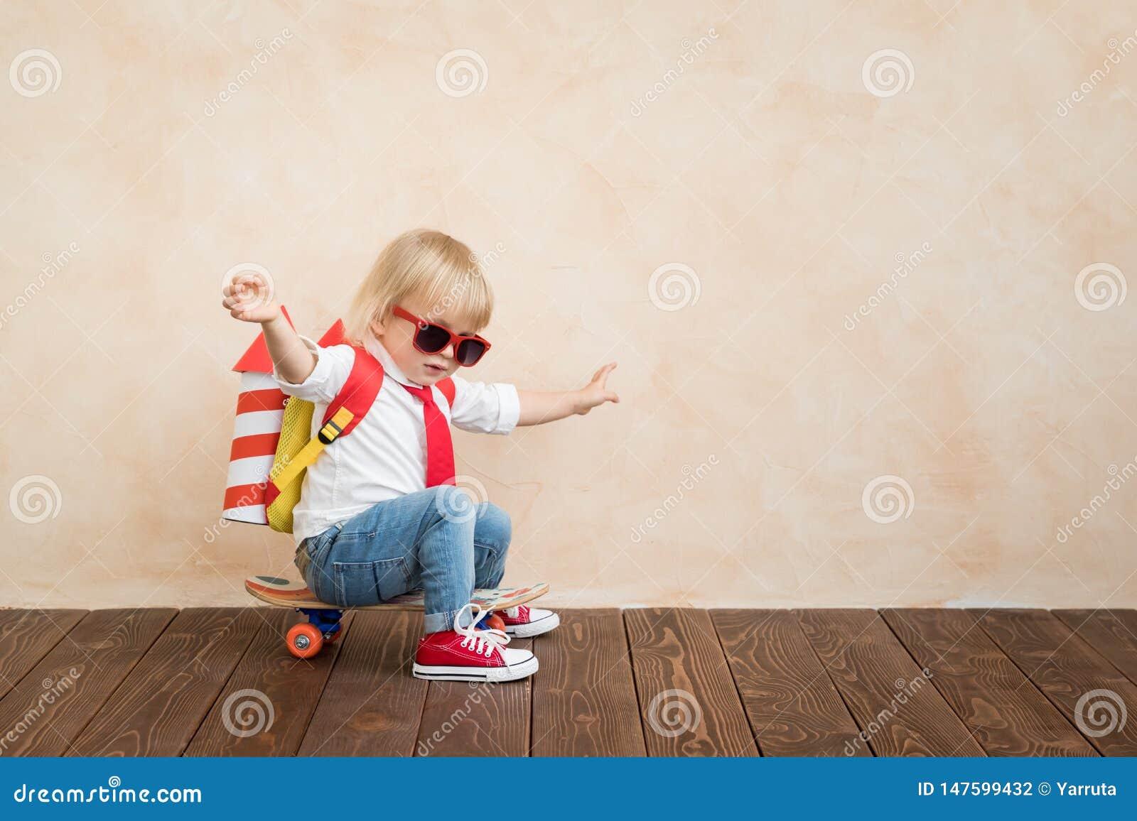 Gl?ckliches Kind, das zu Hause mit Spielzeugrakete spielt