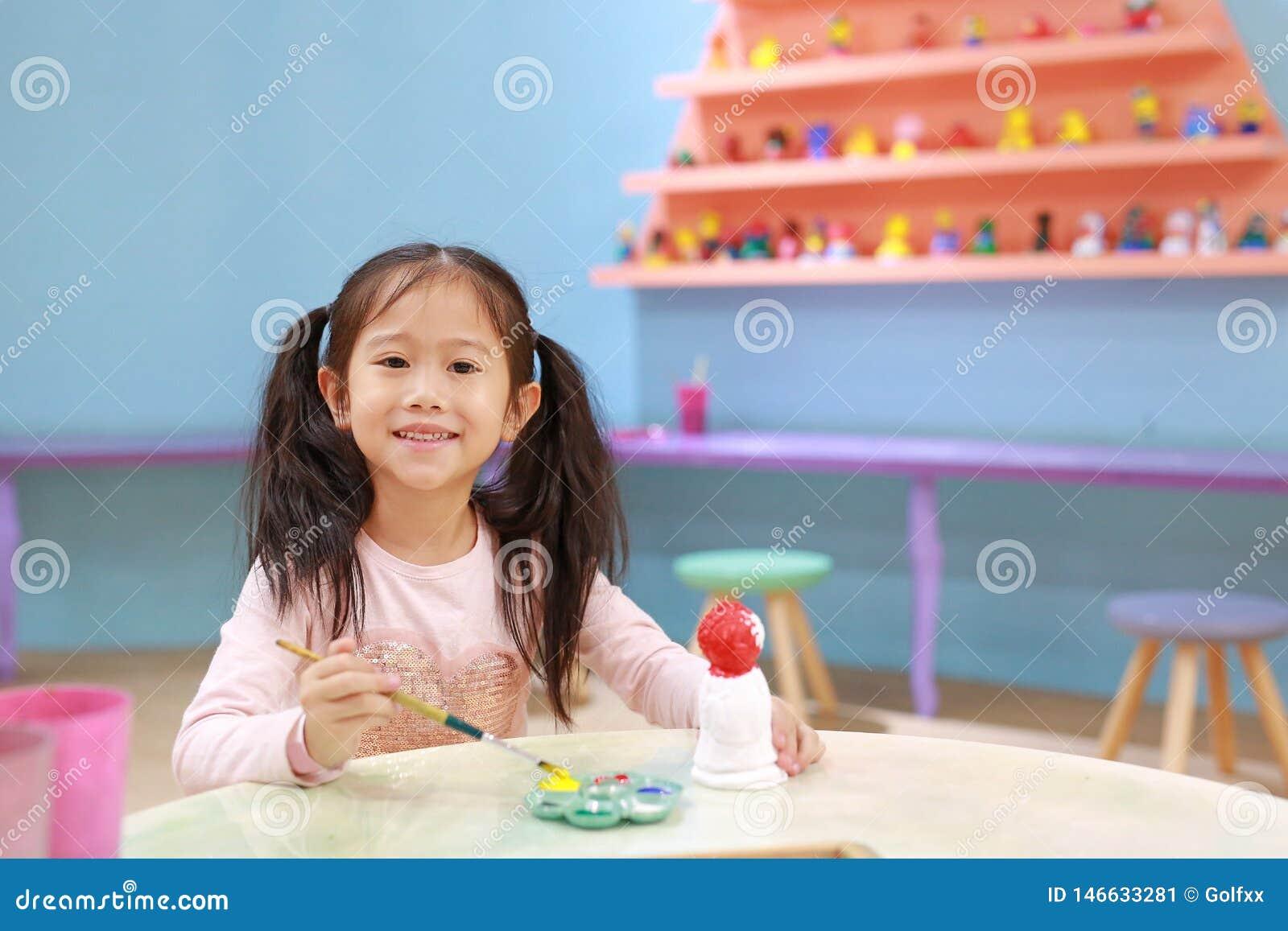 Gl?ckliches kleines Kinderm?dchen, das auf Stuckpuppe Innen zu malen den Spa?, hat