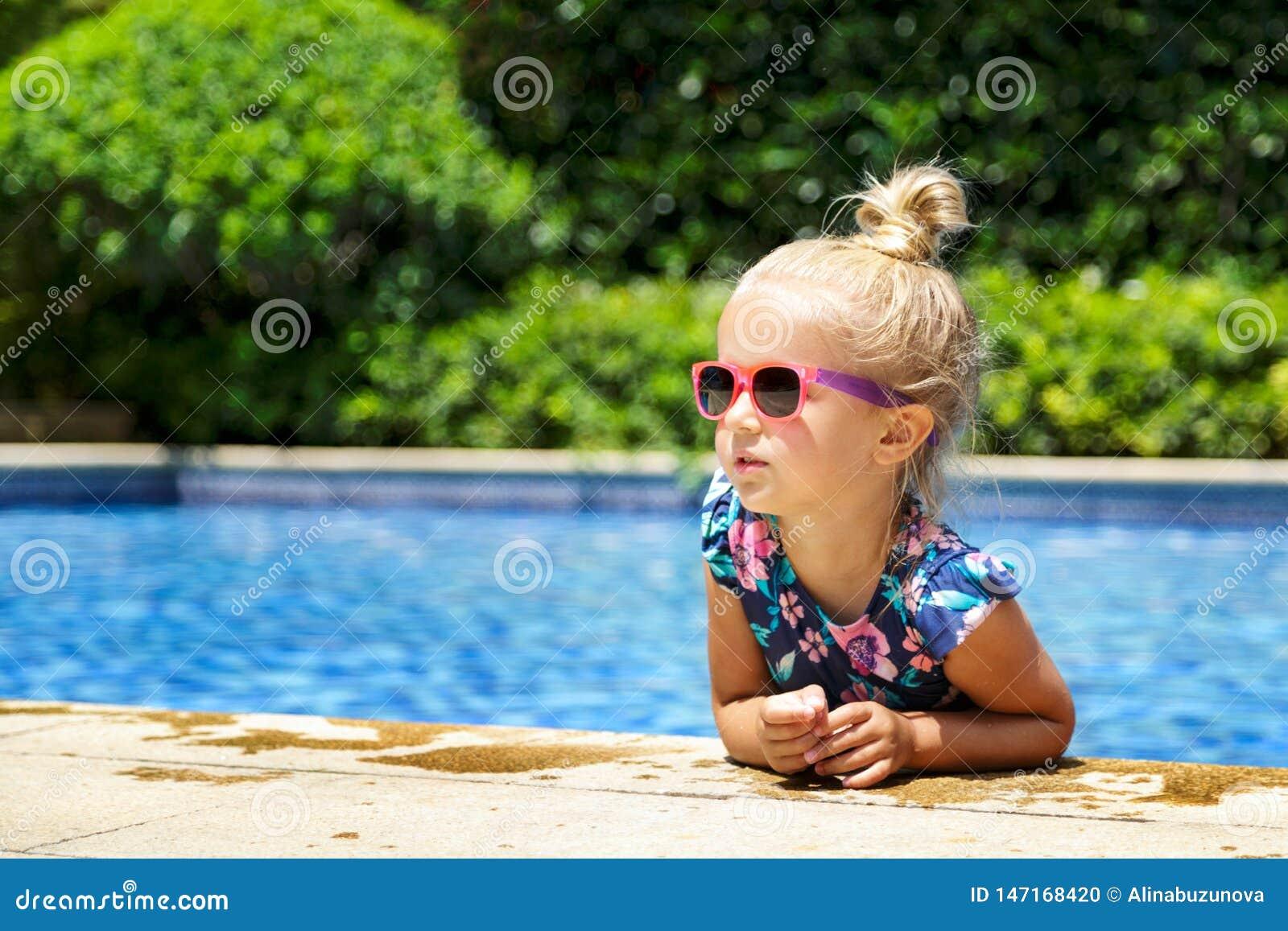 Gl?ckliches kleines M?dchen Swimmingpool im im Freien am hei?en Sommertag Kinder lernen zu schwimmen Kinderspiel im tropischen Er